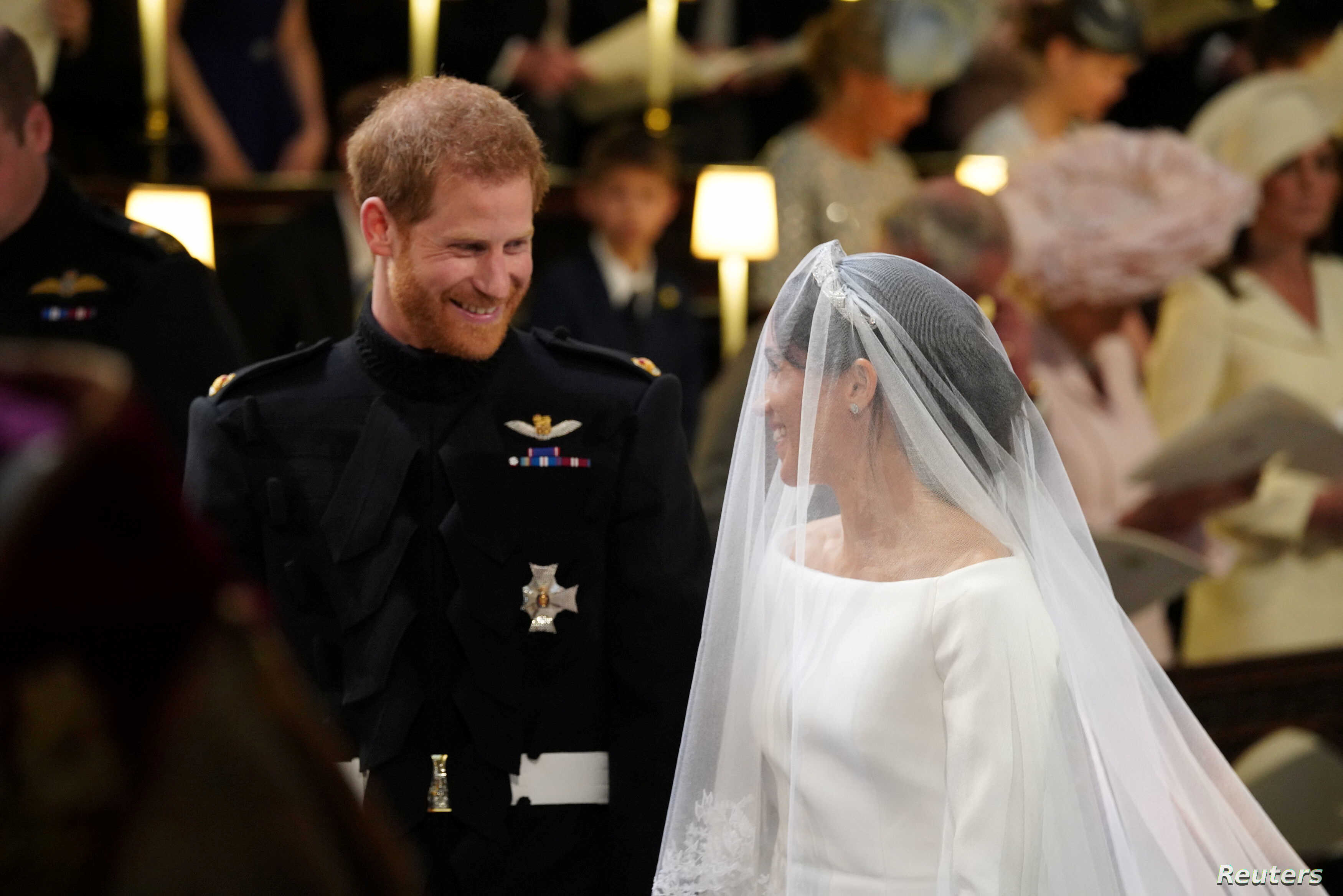 Prince Harry looks at his bride, Meghan Markle, as she arrives accompanied by the Prince of Wales in St George's Chapel at Windsor Castle for their wedding in Windsor, Britain, May 19, 2018.