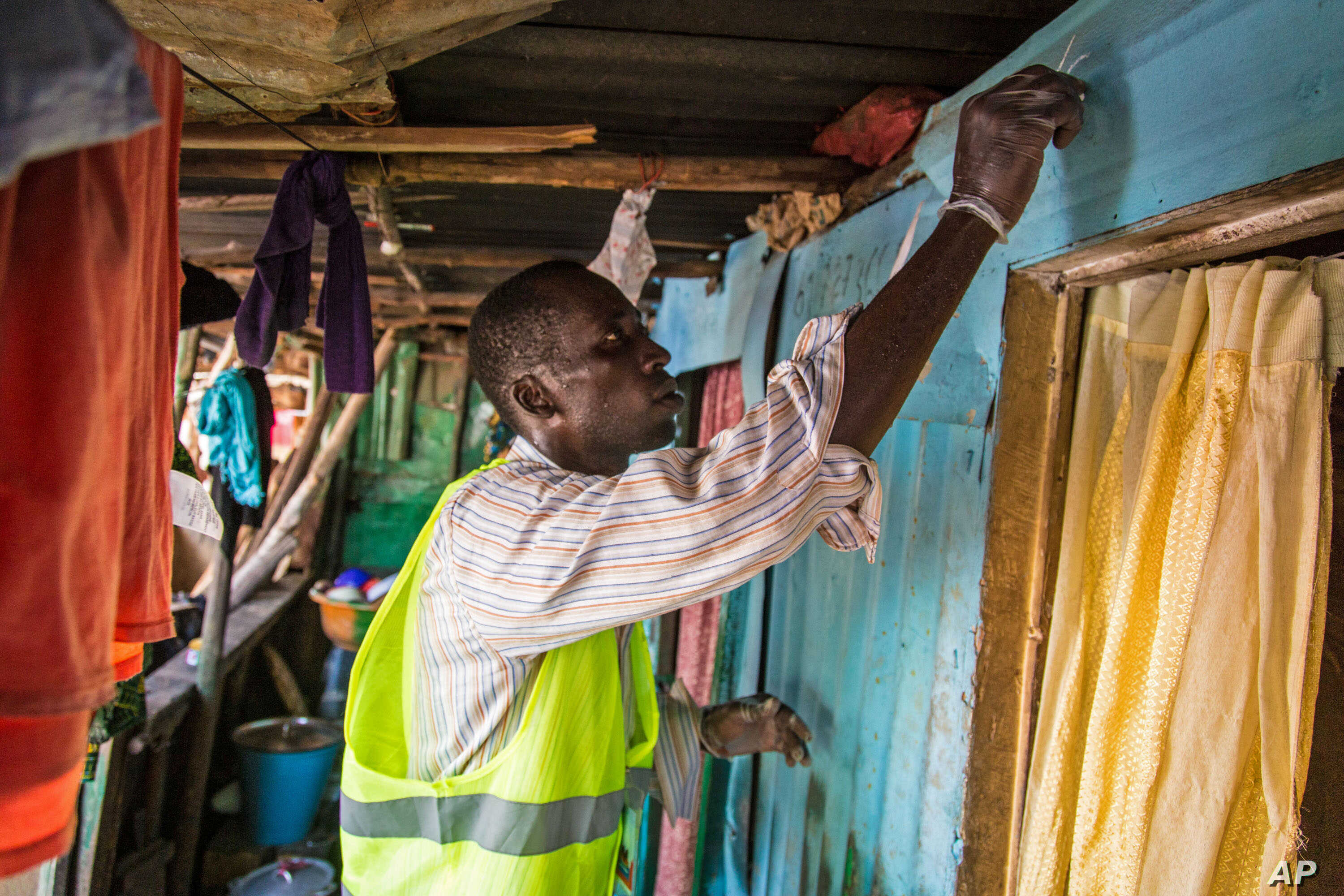 A health worker volunteer marks a home with chalk to identify that it has been visited, as they distribute bars of soap and information about Ebola in Freetown, Sierra Leone, Sept. 20, 2014.