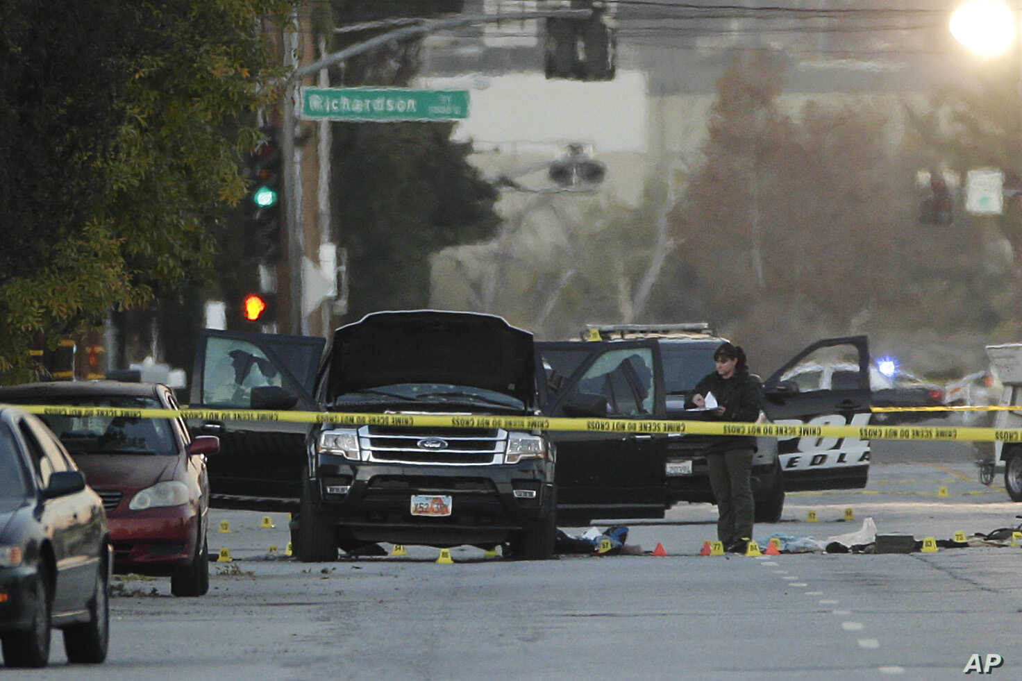 An investigator looks at a Black SUV that was involved in a police shootout with suspects, Dec. 3, 2015, in San Bernardino, Calif.