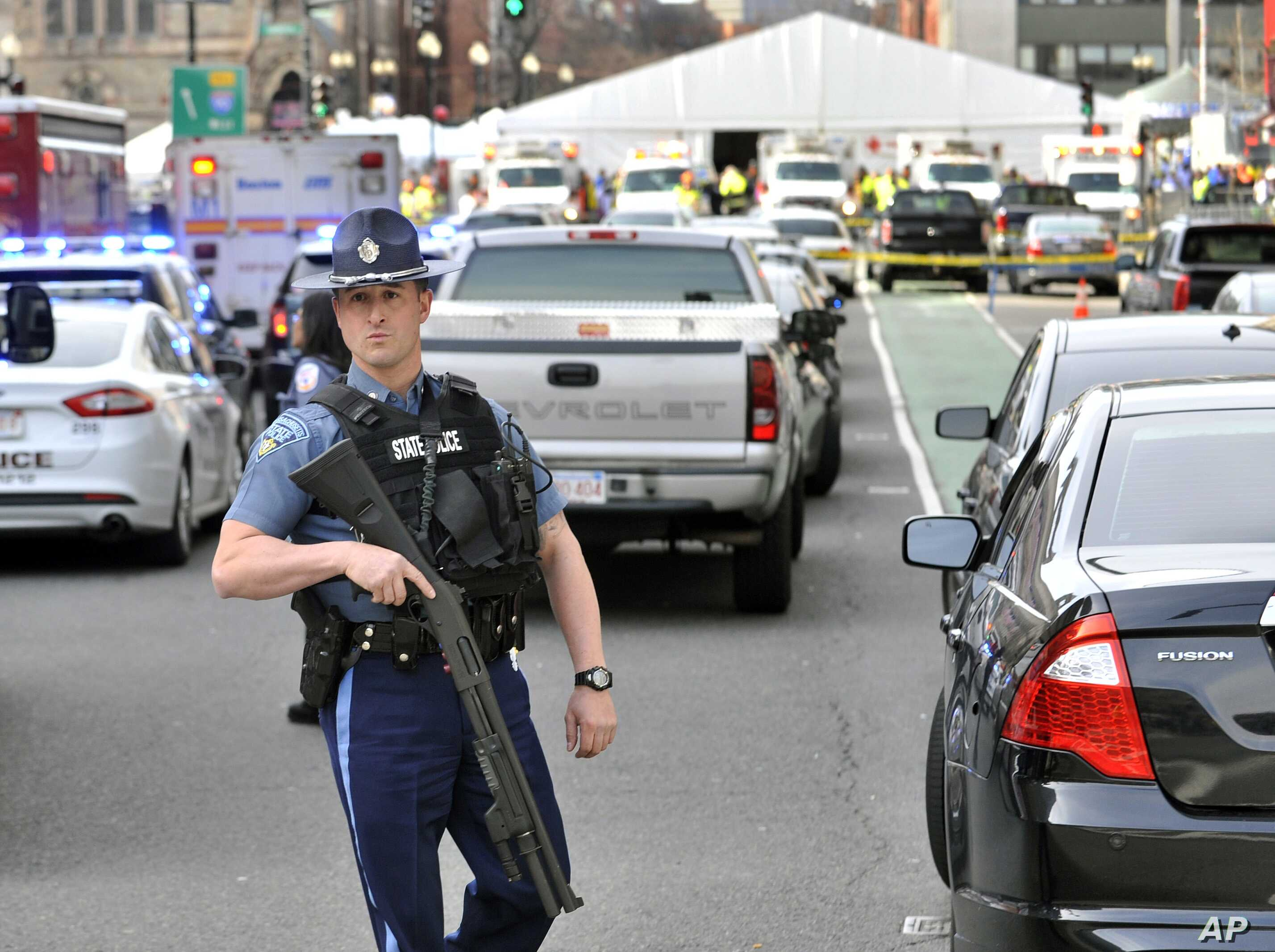 A Massachusetts State Police officer guards the area containing the medical tent, rear, following an explosion at the 2013 Boston Marathon, April 15, 2013.