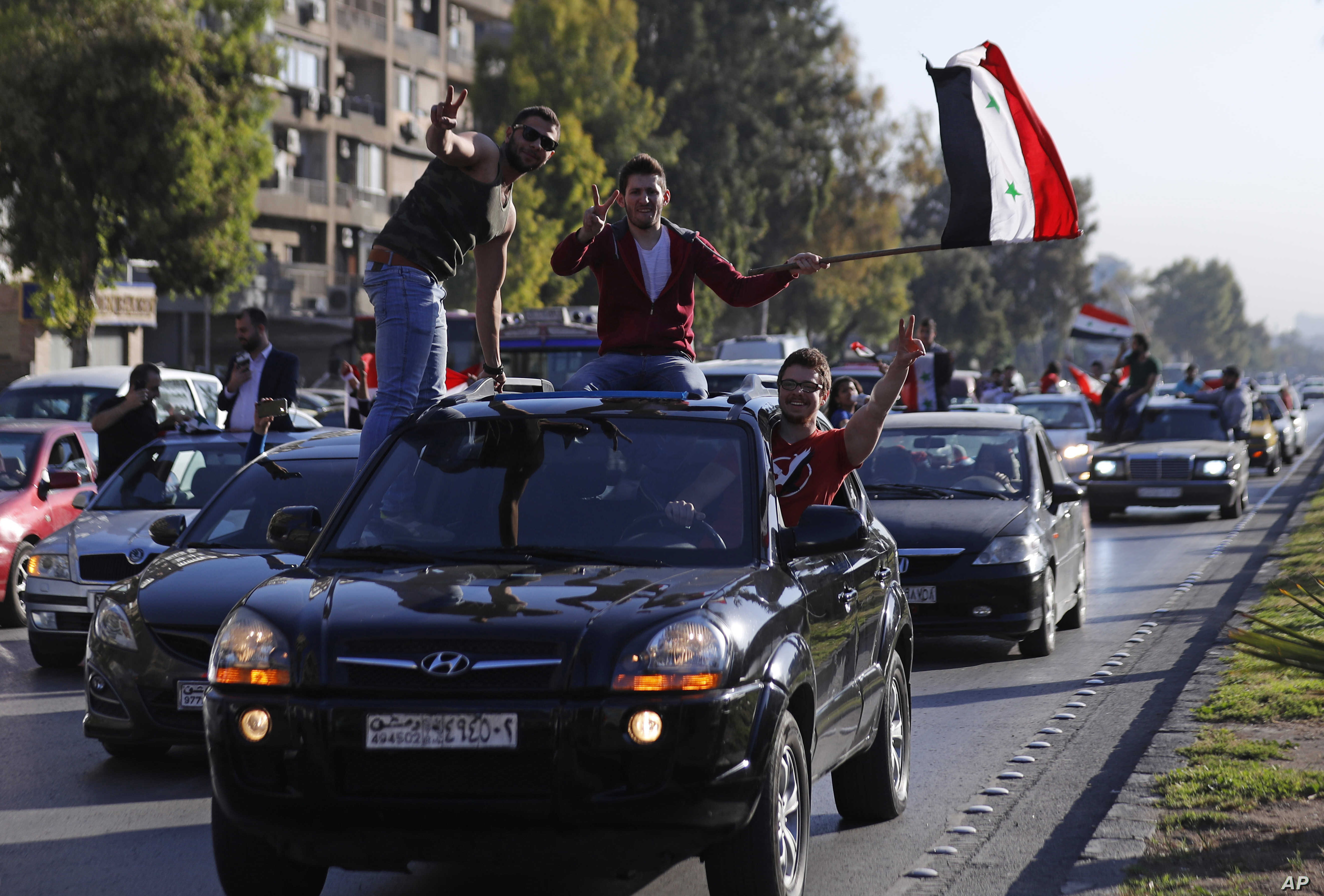 Hundreds of Syrians wave national flags and chant slogans against U.S. President Trump, April 14, 2018, following a wave of U.S., British and French military strikes to punish President Bashar Assad for suspected chemical attack against civilians, in...