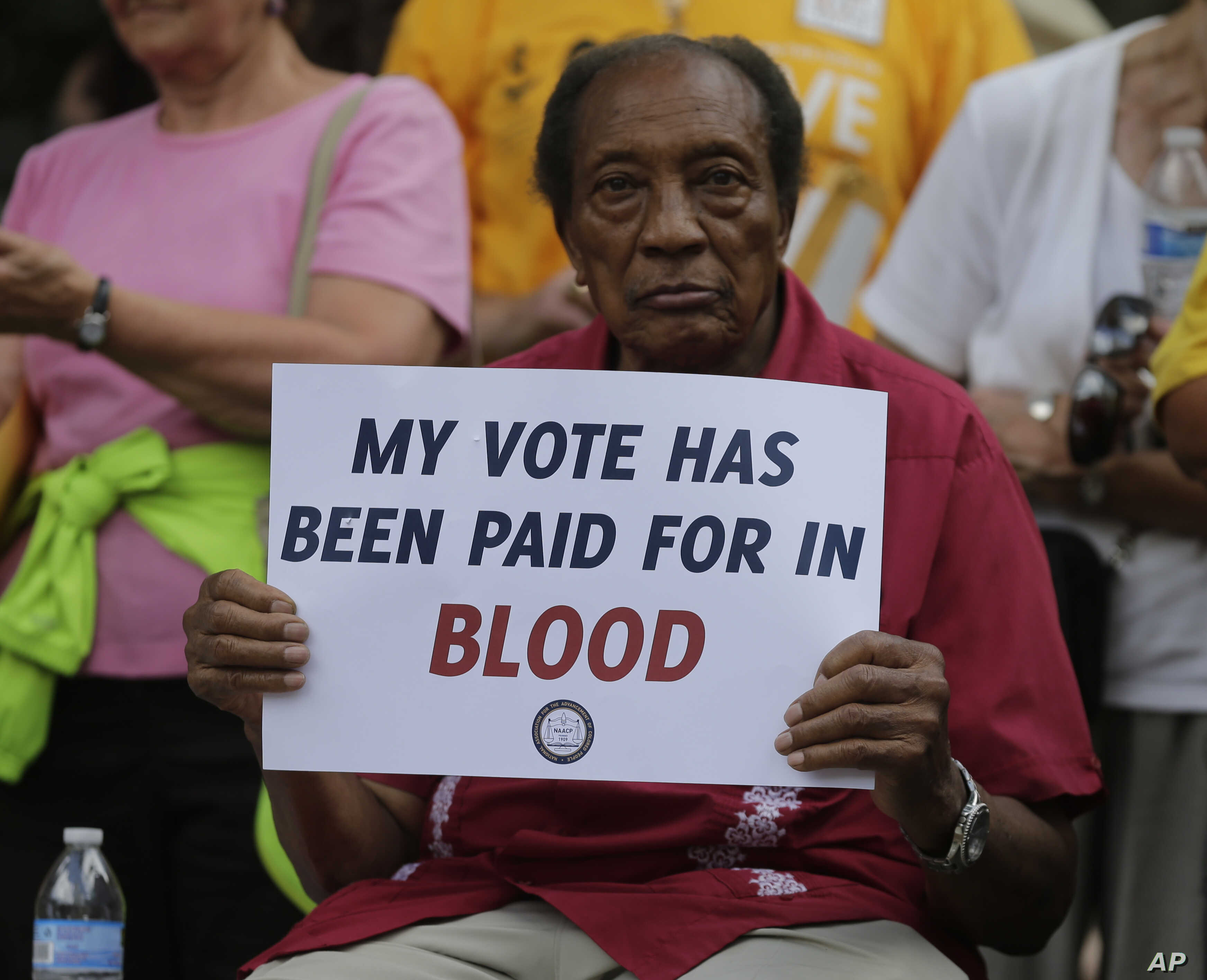 A man holds a protest sign at rally in Winston-Salem, North Carolina, after the start of a federal trial challenging the state's voting rights law, July 13, 2015.