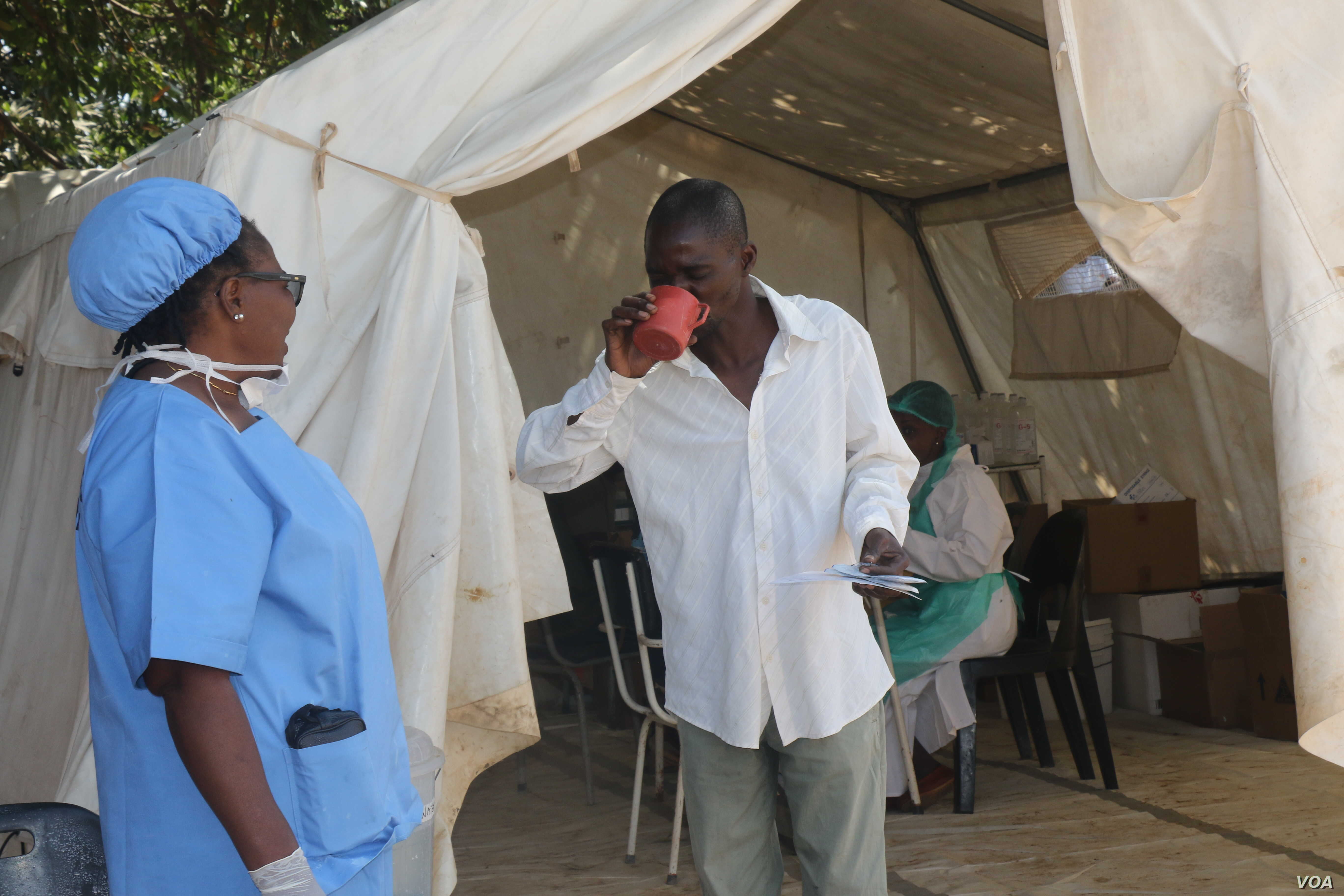 A medical staff member (left) administers oral rehydrating solution to a cholera patient to replace fluids he lost through diarrhea, in Harare, Zimbabwe, Sept. 12, 2018, (C. Mavhunga/VOA)