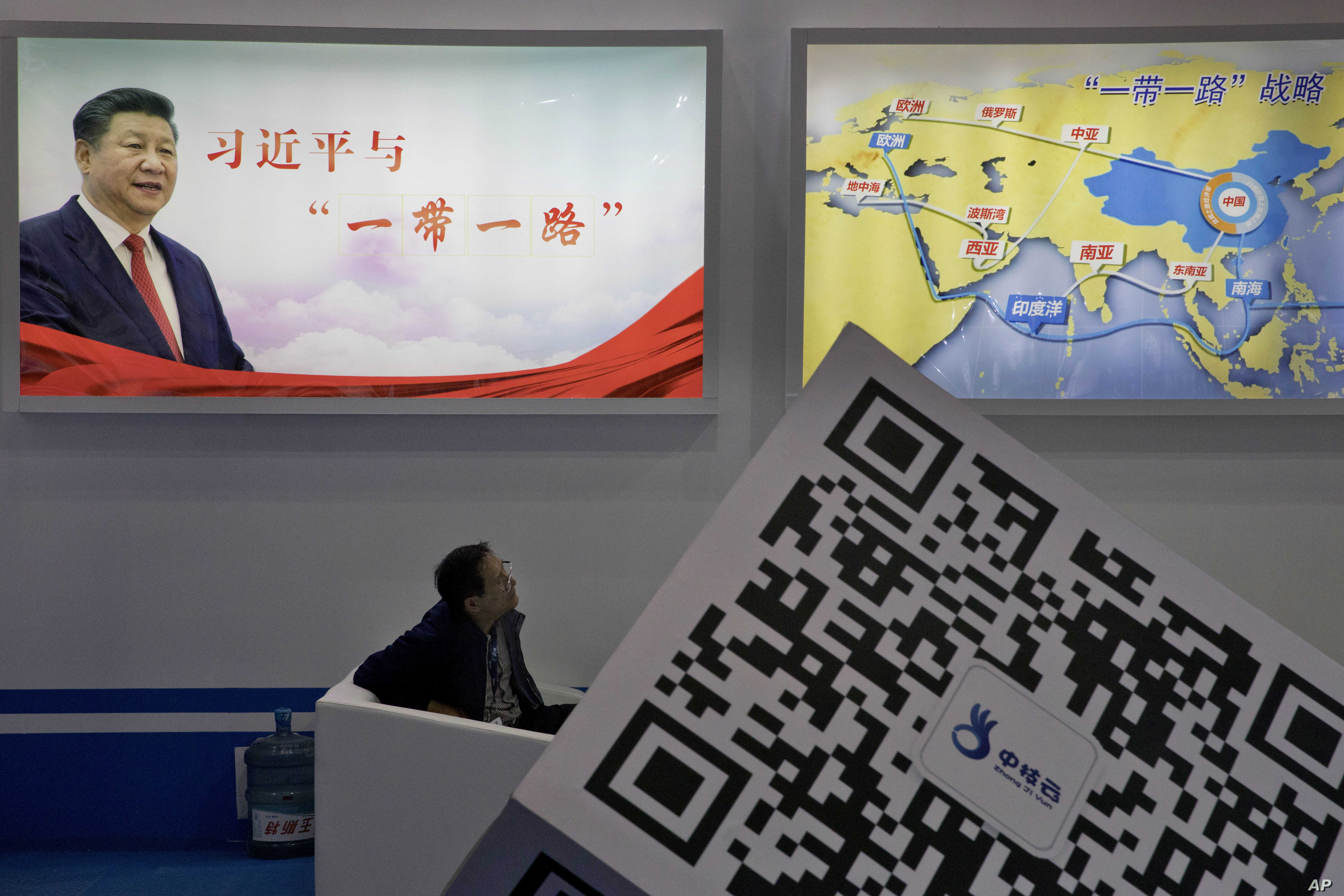 "An attendee at a conference looks up near a portrait of Chinese President Xi Jinping with the words ""Xi Jinping and One Belt One Road"" and ""One Belt One Road strategy,"" in Beijing, April 28, 2017. The ""Belt and Road Forum"" opening Sunday is the l..."