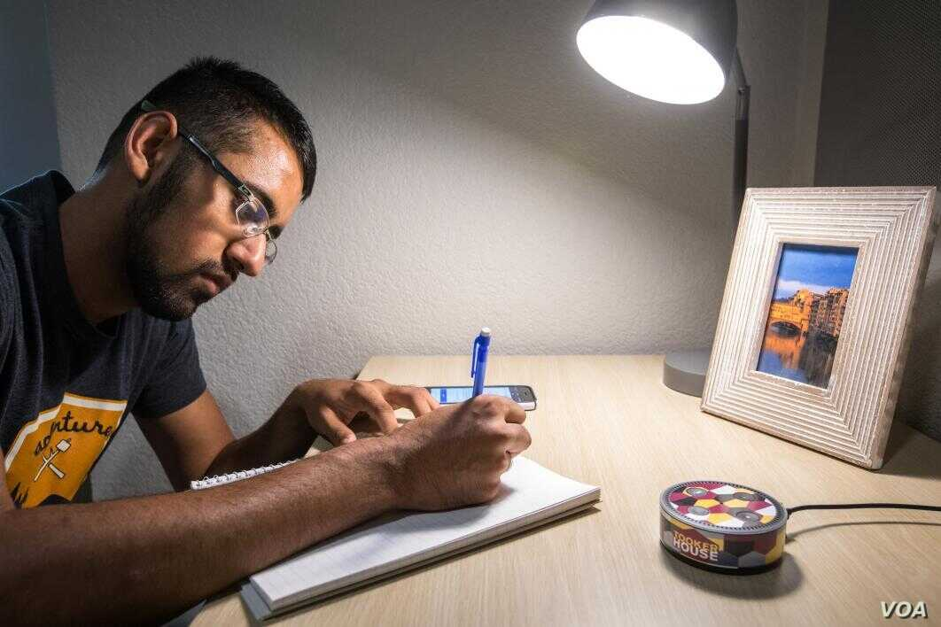 Bhavik Patel, a mechanical engineering senior and peer mentor at Arizona State's community housing center Tooker House, demonstrates use of an Amazon Echo Dot while working on formulas. (Charlie Leight/ASU Now)