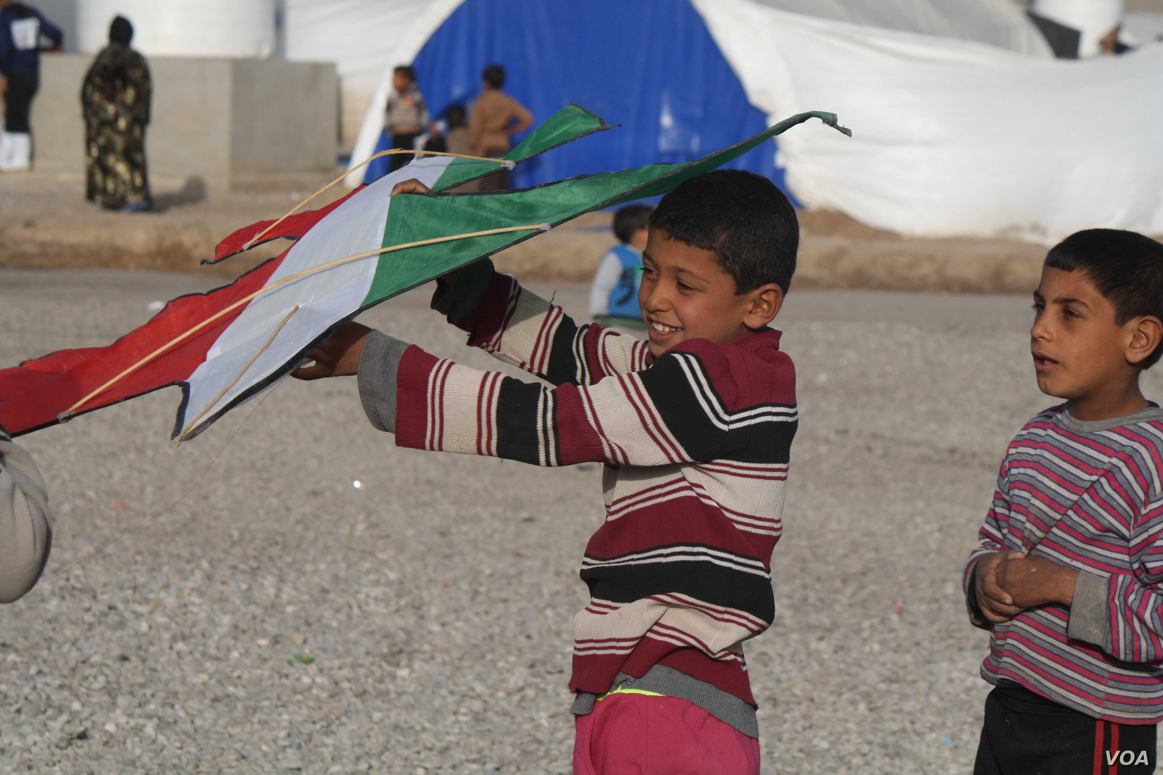 Children in camp pass time playing with kites given to them by Kurdish peshmerga soldiers in Hassan Shams, Kurdish Iraq, Jan. 10, 2017. (H. Murdock/VOA)