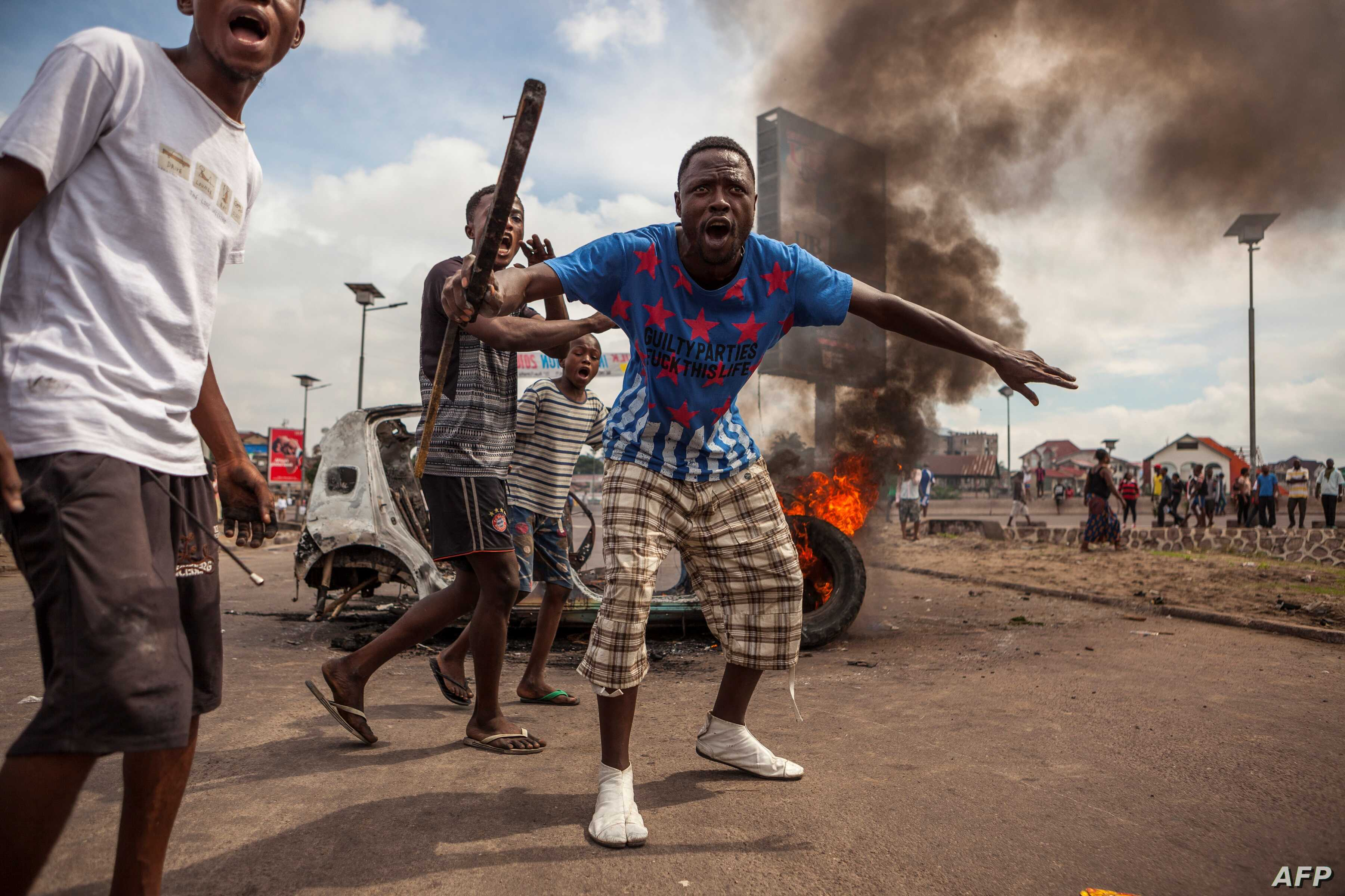 Demonstrators gather in front of a burning car during an opposition rally in Kinshasa, DRC, Sept. 19, 2016.