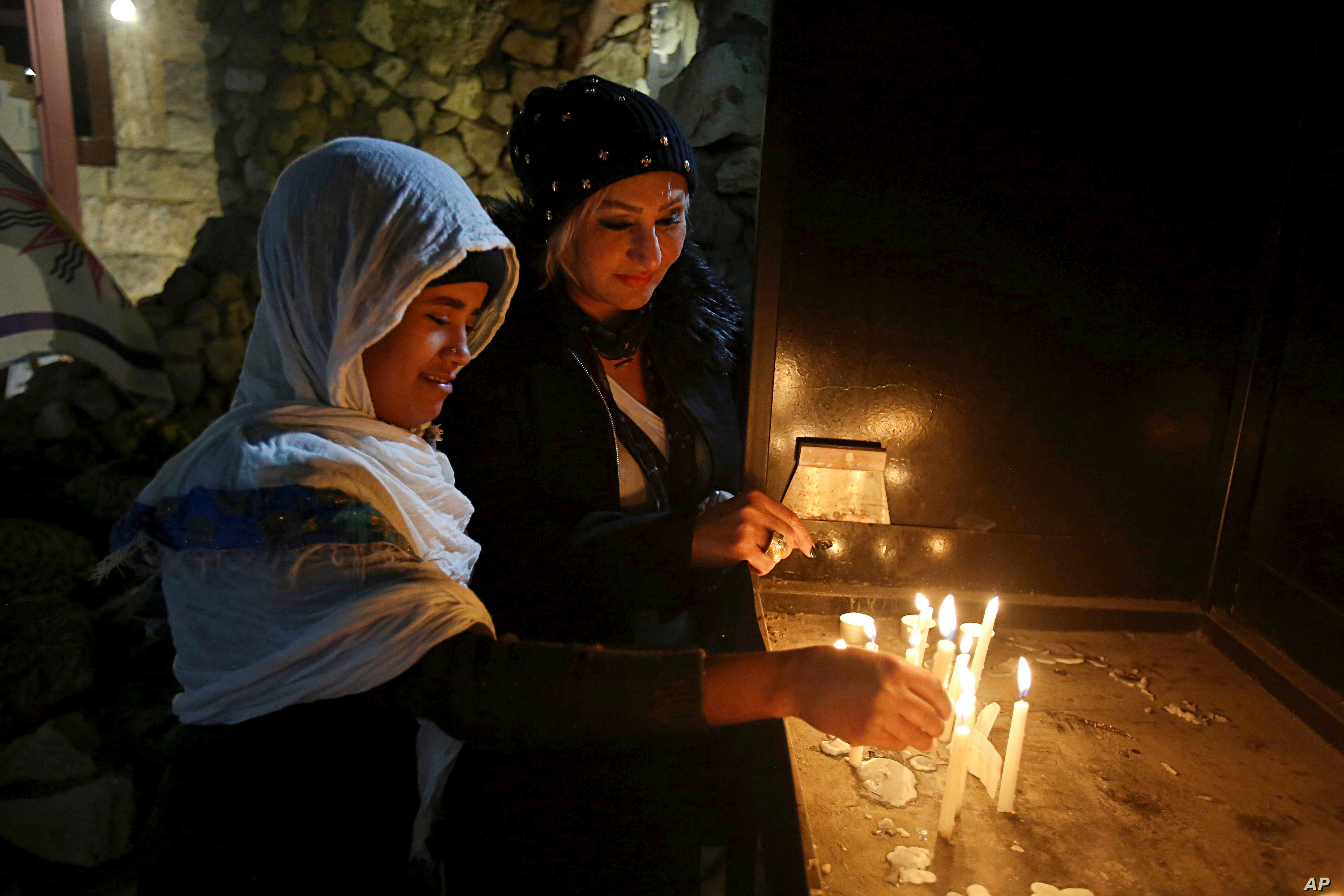 Iraqi Christians light candles after a Christmas Eve Mass in St. Joseph's Church in Baghdad, Iraq, Dec. 24, 2017.