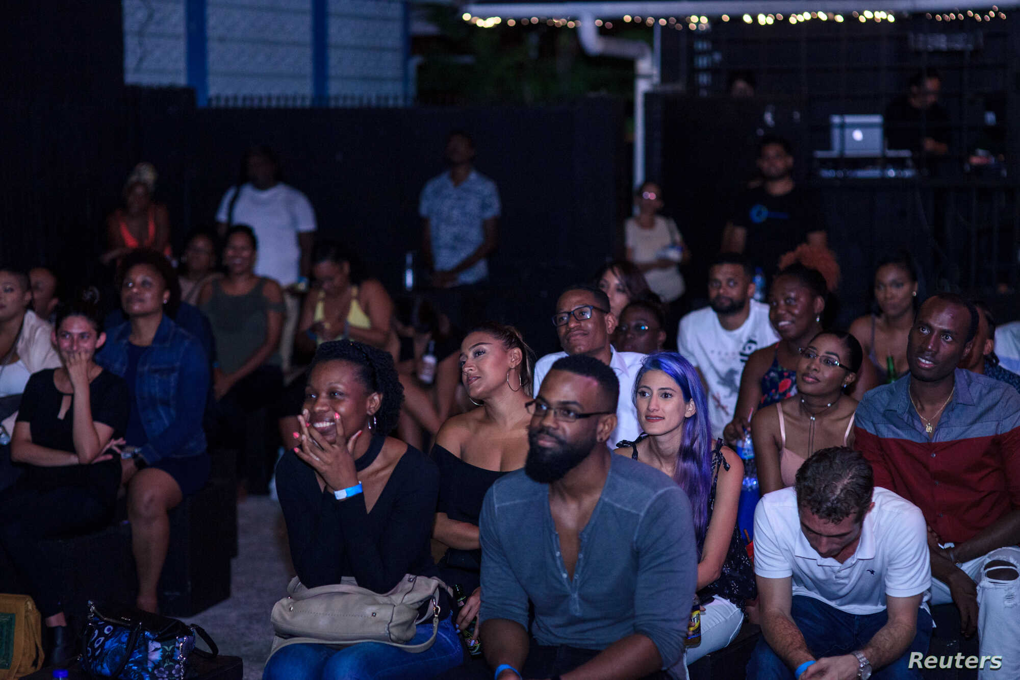 """The audience listens to live poetry at """"True Talk No Lie"""", a monthly spoken word event in Port of Spain, Trinidad and Tobago, May 23, 2018."""