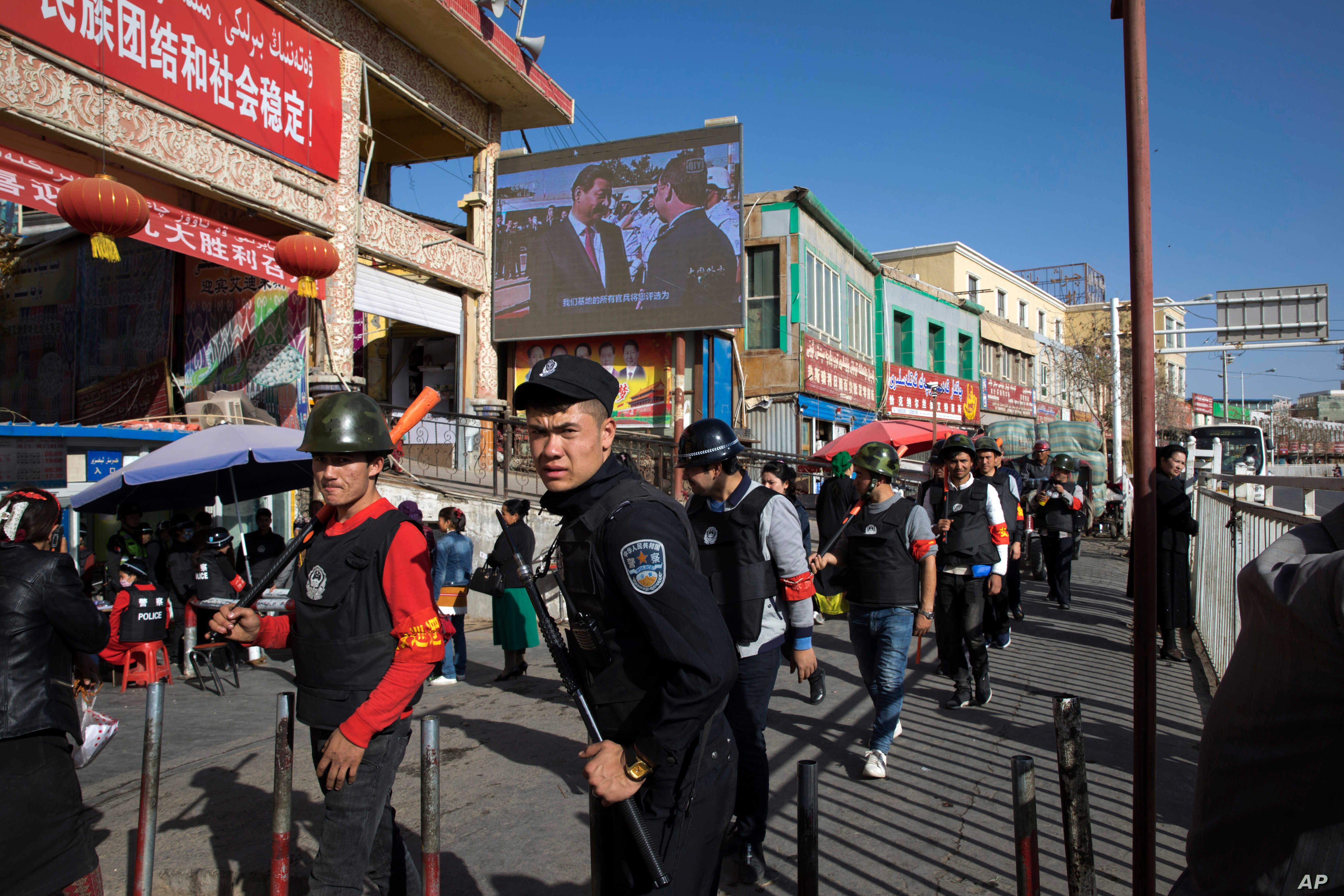 FILE - In this Nov. 3, 2017, photo, armed civilians patrol the area outside the Hotan Bazaar where a screen shows Chinese President Xi Jinping in Hotan, in western China's Xinjiang region.  Acting Deputy Assistant Secretary of State Laura Stone said ...