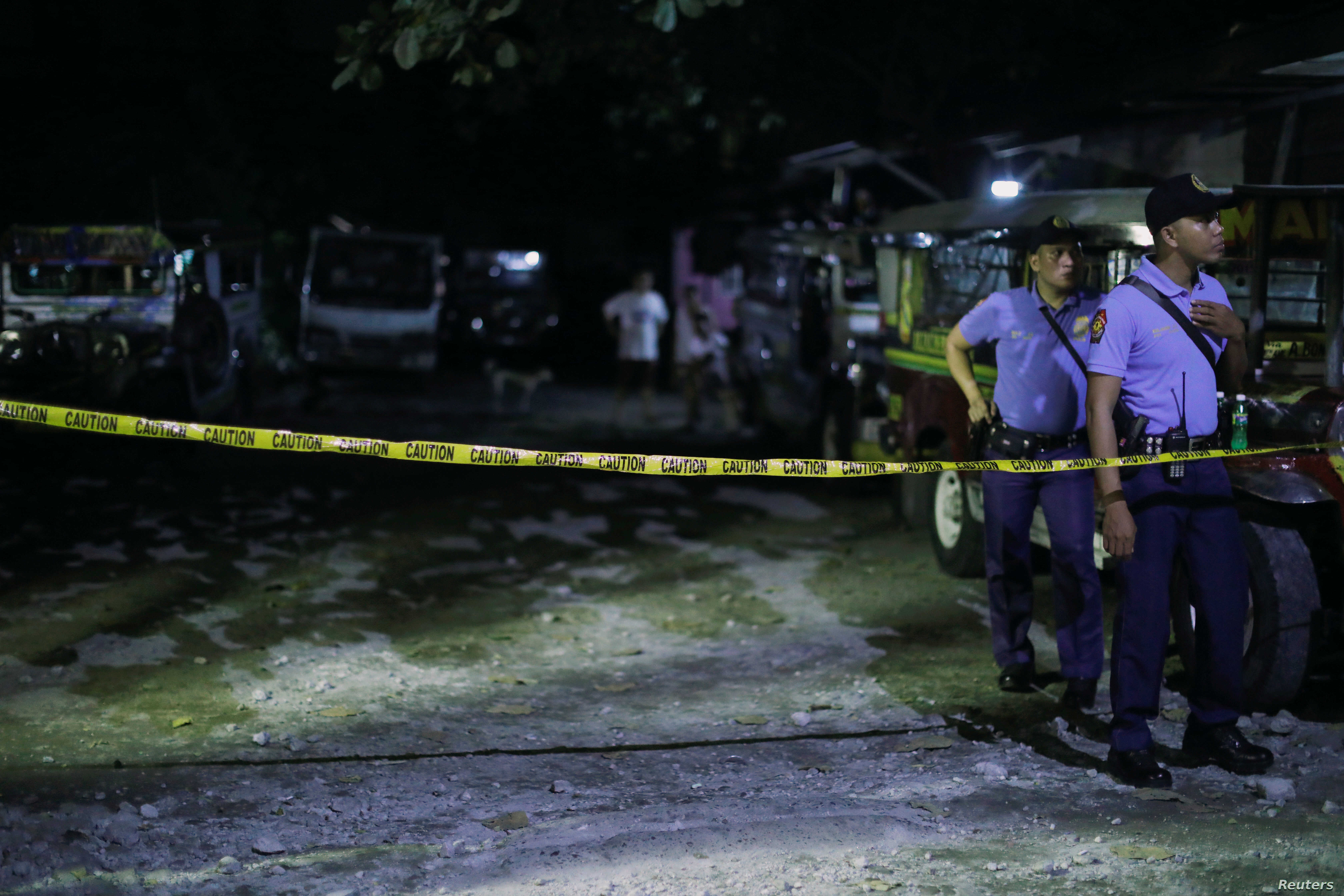 Police officers stand behind a police line after a man was killed during a police anti-drug operation in Caloocan city, Metro Manila, Philippines, Aug. 17, 2017.