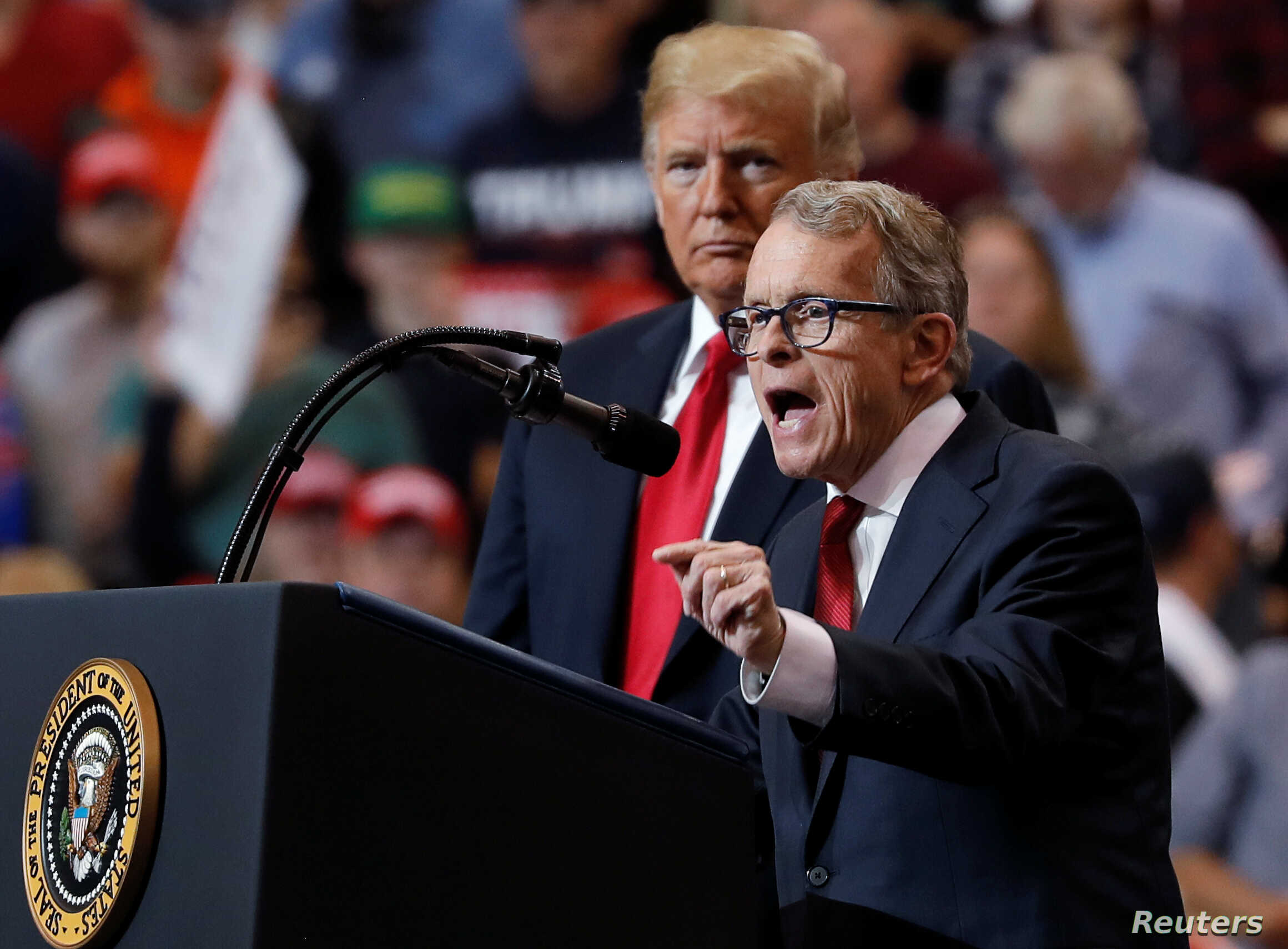 U.S. President Donald Trump listens as Ohio gubernatorial nominee and Ohio Attorney General Mike Dewine speaks during a campaign rally in Cleveland, Ohio., Nov. 5, 2018.
