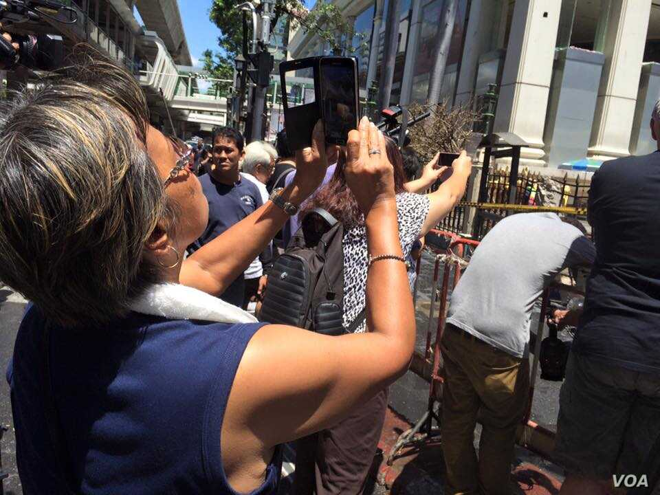 """People take """"selfies"""" in front of the Erawan Shrine, location of a bomb blast in central Bangkok, Thailand, Aug. 18, 2015. (Photo: Steve Herman / VOA)"""