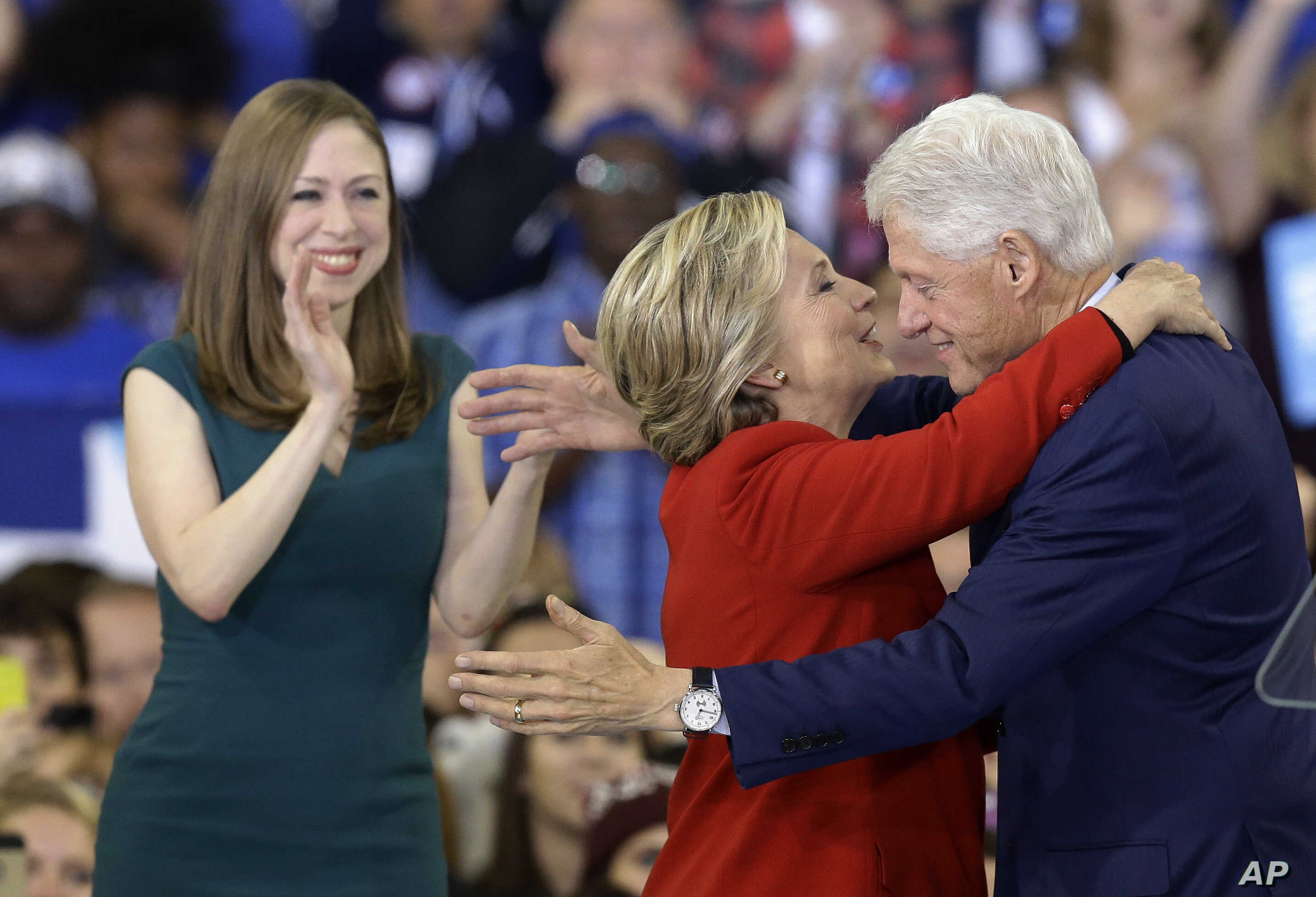 Democratic presidential candidate Hillary Clinton hugs her husband, former President Bill Clinton as their daughter Chelsea Clinton looks on during a campaign rally in Raleigh, N.C., Nov. 8, 2016.