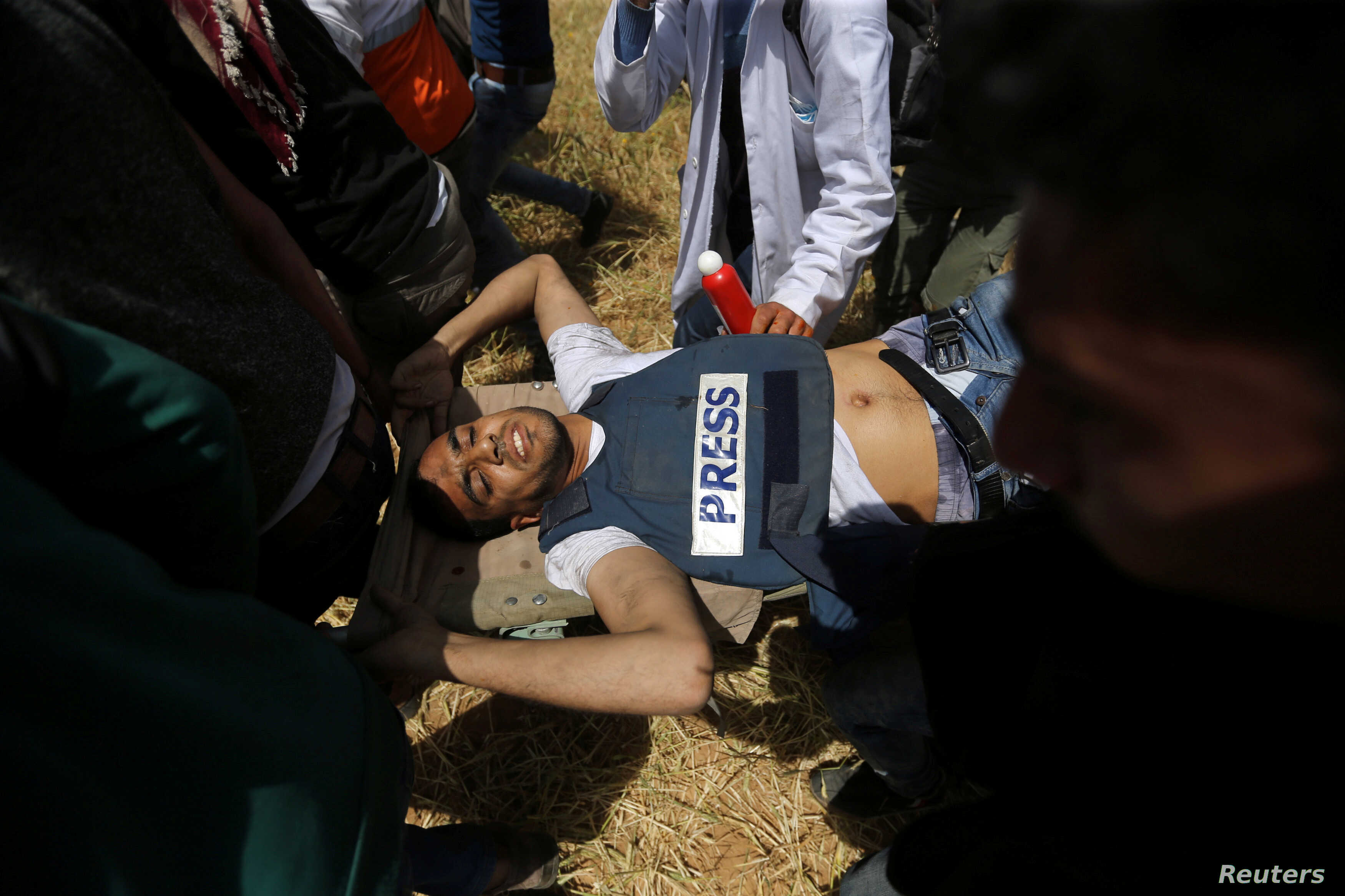 Palestinians evacuate a wounded journalist during clashes with Israeli troops at the Israel-Gaza border at a protest demanding the right to return to their homeland, in the southern Gaza Strip April 6, 2018.