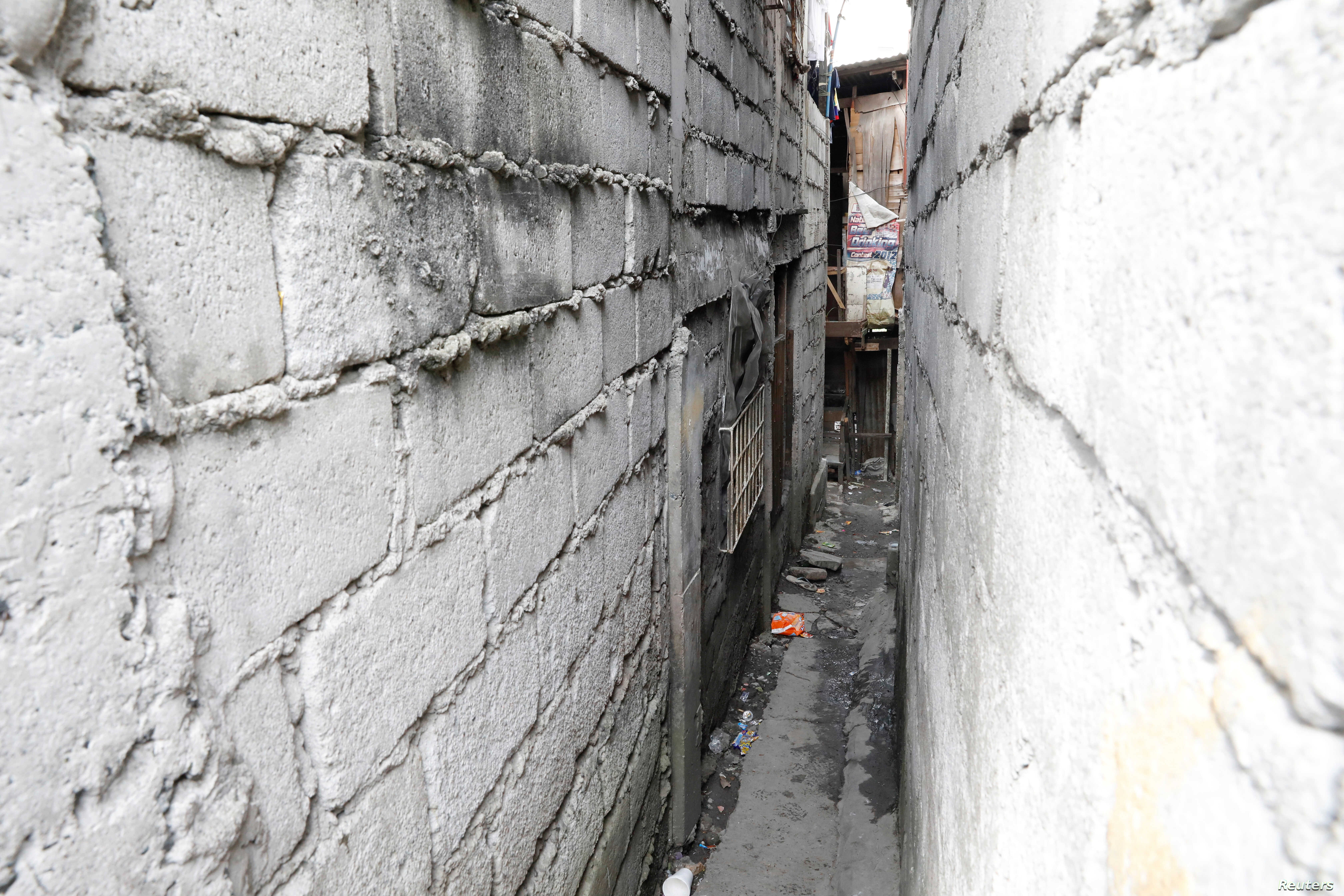 A small alley with a door on the far end on the left leads to a drug den in Manila, Philippines, Feb. 13, 2017.