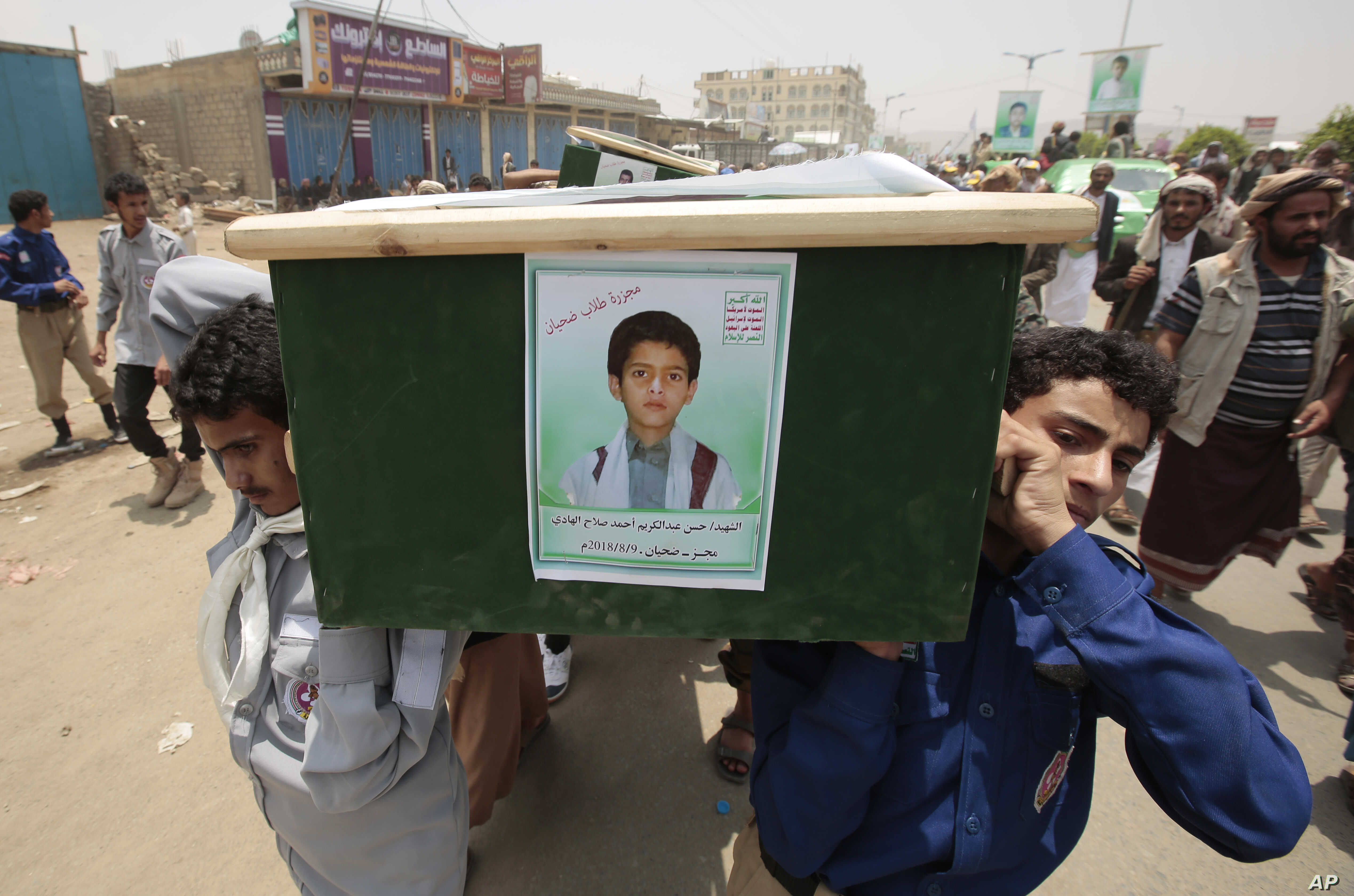 FILE - Yemeni men carry the coffin of a boy who was killed by a Saudi-led coalition airstrike, during a funeral in Saada, Yemen, Aug. 13, 2018.