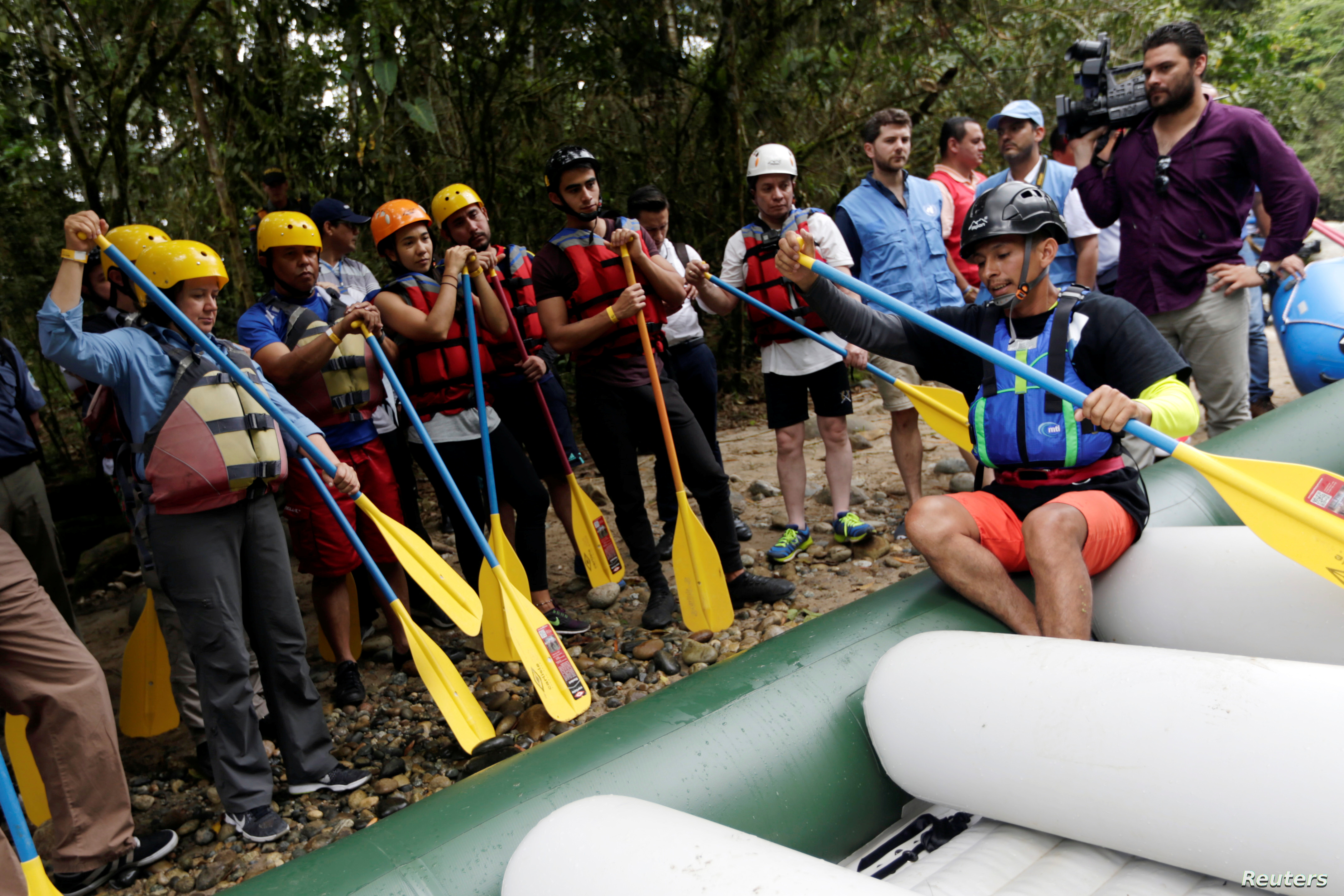 Duberney Moreno, former rebel of the FARC, rafting guide and instructor, speaks with a group of the press and government representatives before boarding an inflatable raft in Miravalle, Colombia, Nov. 9, 2018.