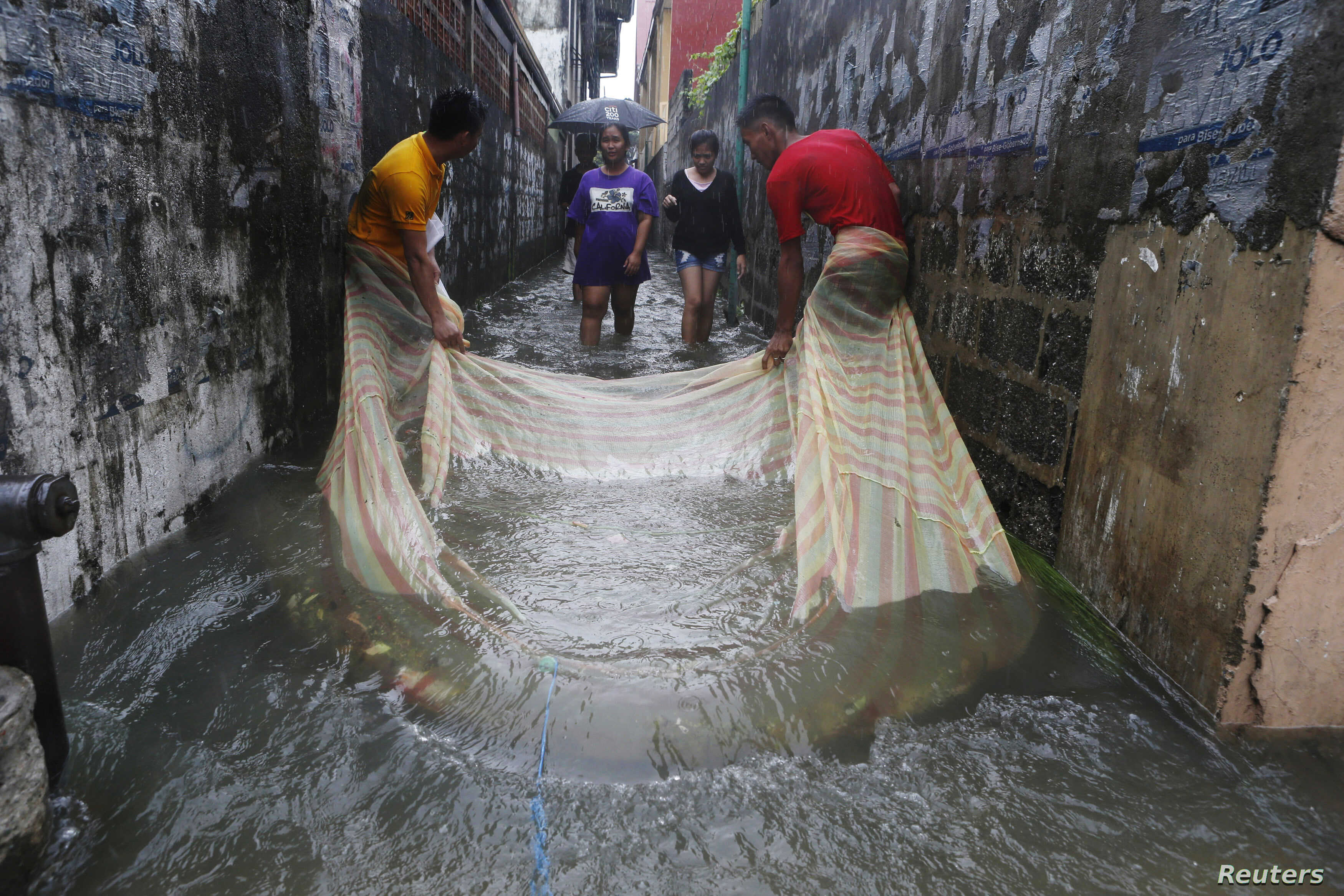 FILE - Men use a mosquito net to catch fish in a flooded alley in a residential district in Bacoor, near Manila, Phillippines, Aug. 20, 2013.