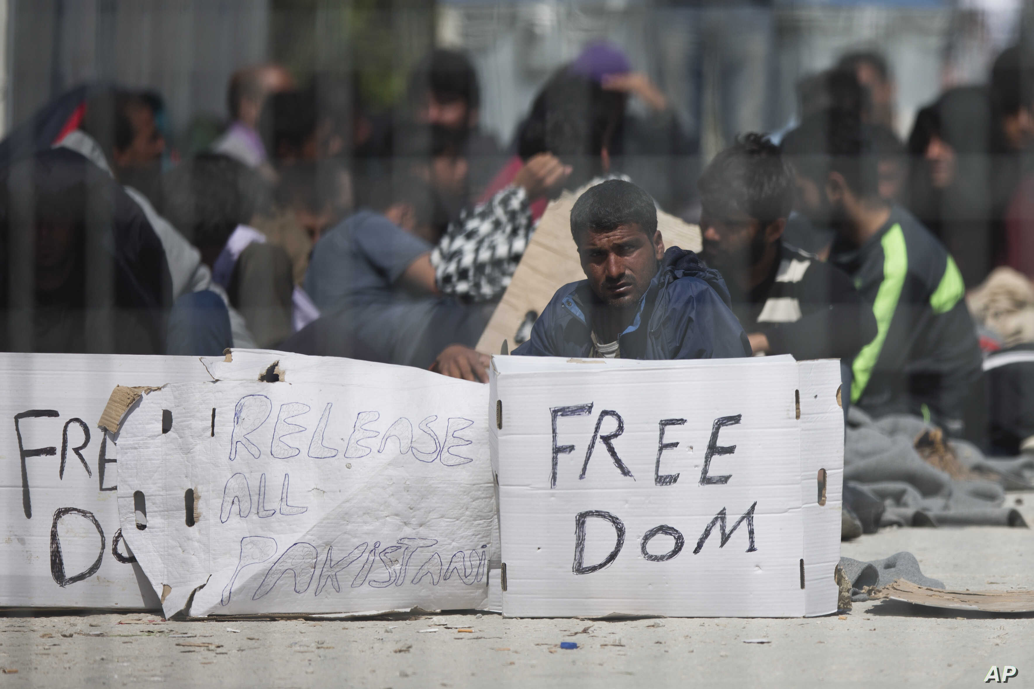 Seen through a wire fence, refugees and migrants most of them from Pakistan, hold placards during a third day of  hunger strike to protest their deportation to Turkey, in the Greek island of Lesbos, April 7, 2016.