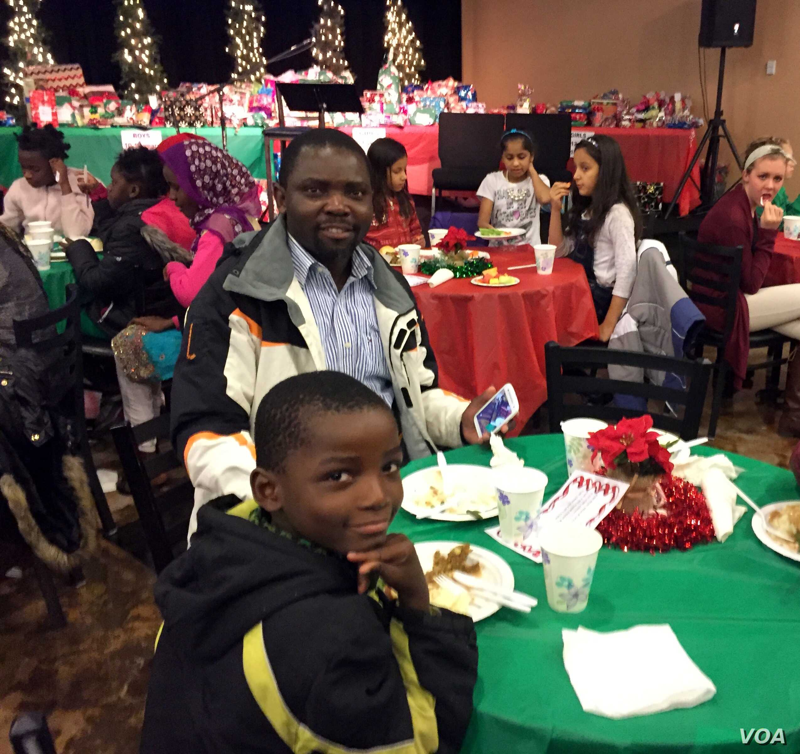 "Akembe Bilombele, center, fled war-torn Congo with his family and was resettled in Twin Falls, Idaho, four months ago. ""People in Idaho are very kind,"" he said at a church Christmas party. ""I am very happy here."""