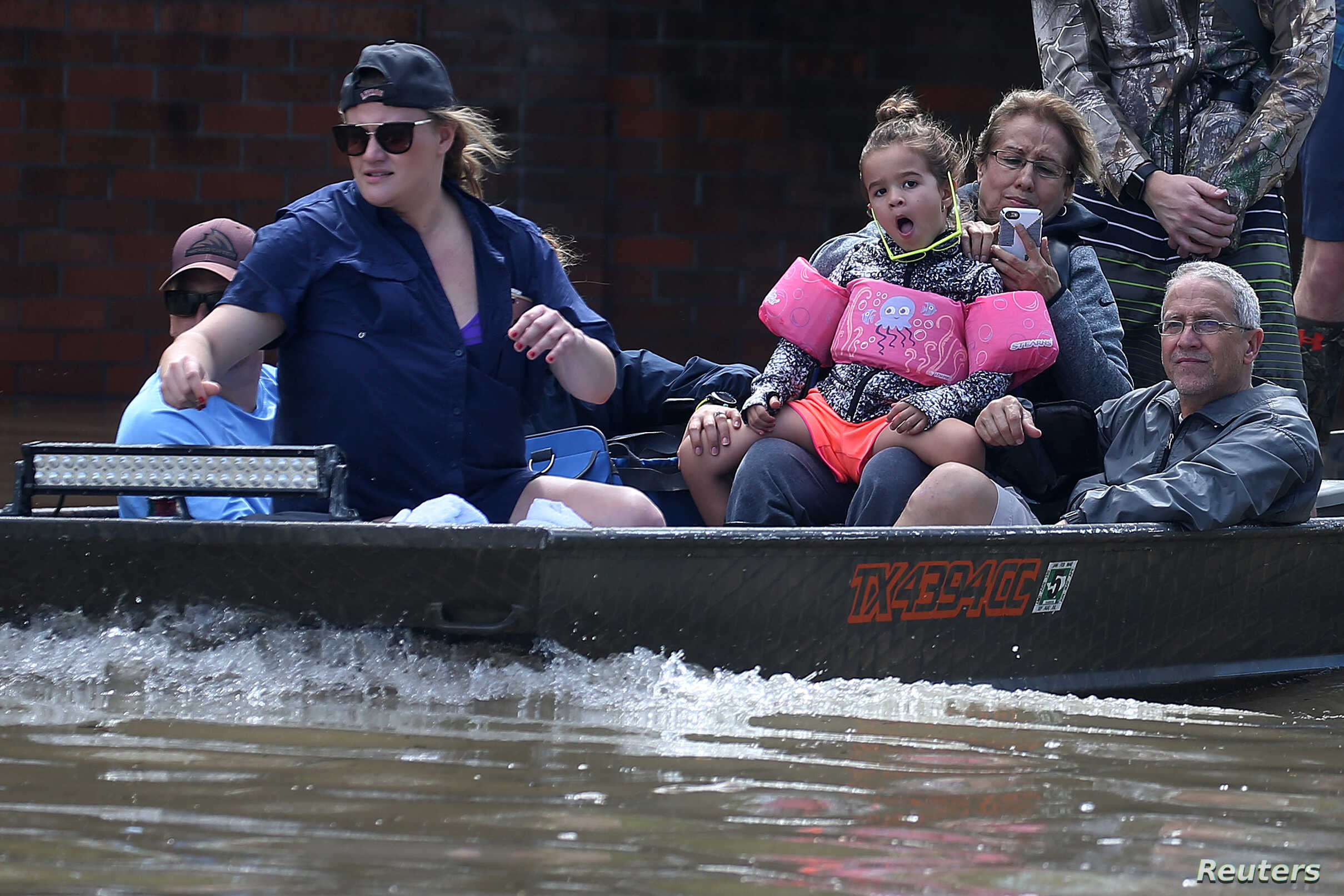 People ride a boat though flood water after being evacuated from the rising water following Hurricane Harvey in a neighborhood west of Houston, Texas, U.S., August 30, 2017.