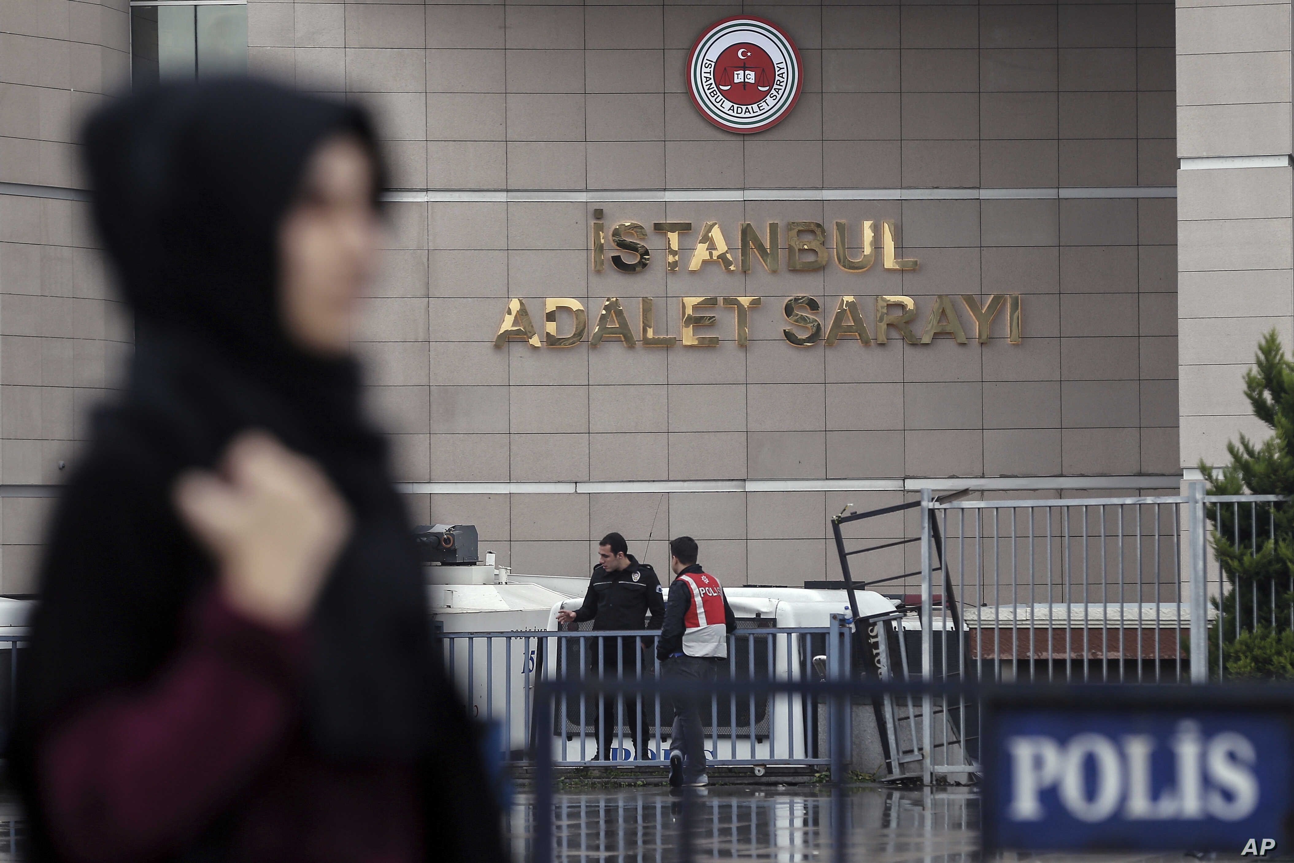 A woman walks along a security barricade outside the main courthouse in Istanbul, Turkey, Oct. 24, 2017.