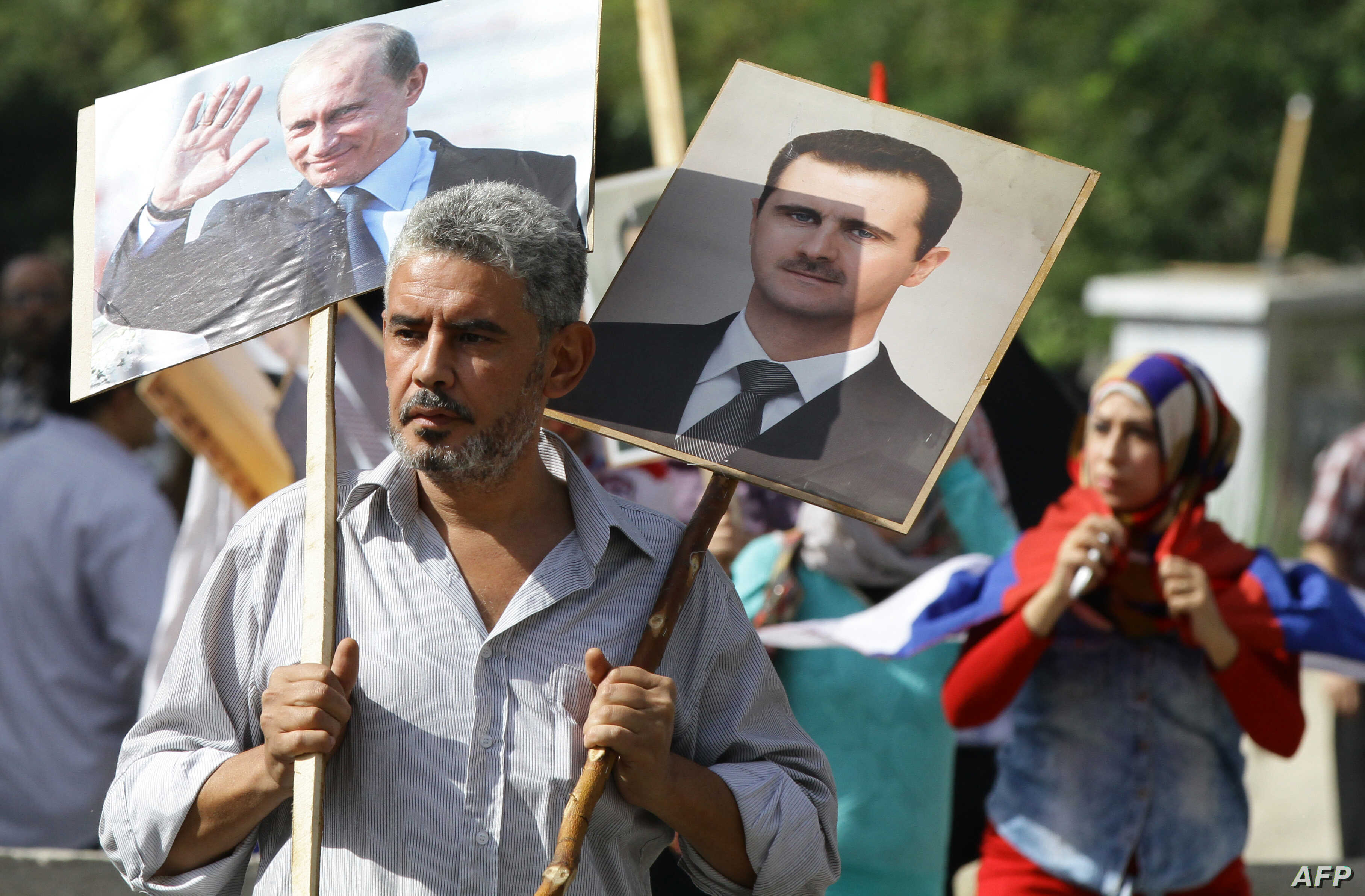 A Syrian man holds portraits of President Bashar al-Assad, right, and Russian President Valdimir Putin, left, as several hundred people gathered near the Russian Embassy in Damascus to express their support for Moscow's air war in Syria, just before ...