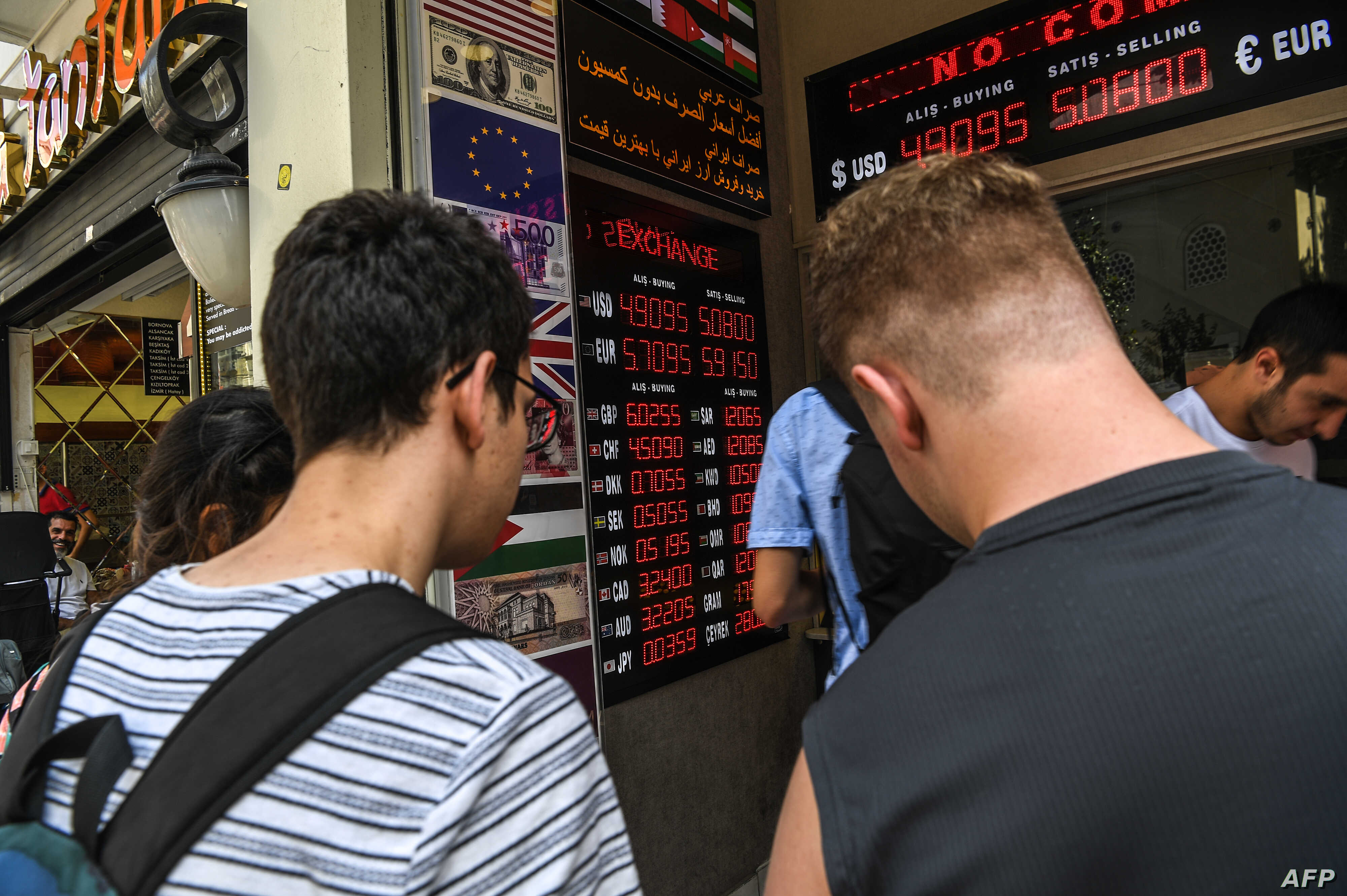 People change their money at a counter on the Istiklal avenue in Istanbul on Aug. 2, 2018 next to a panel indicating foreign exchange and Turkish lira rates.