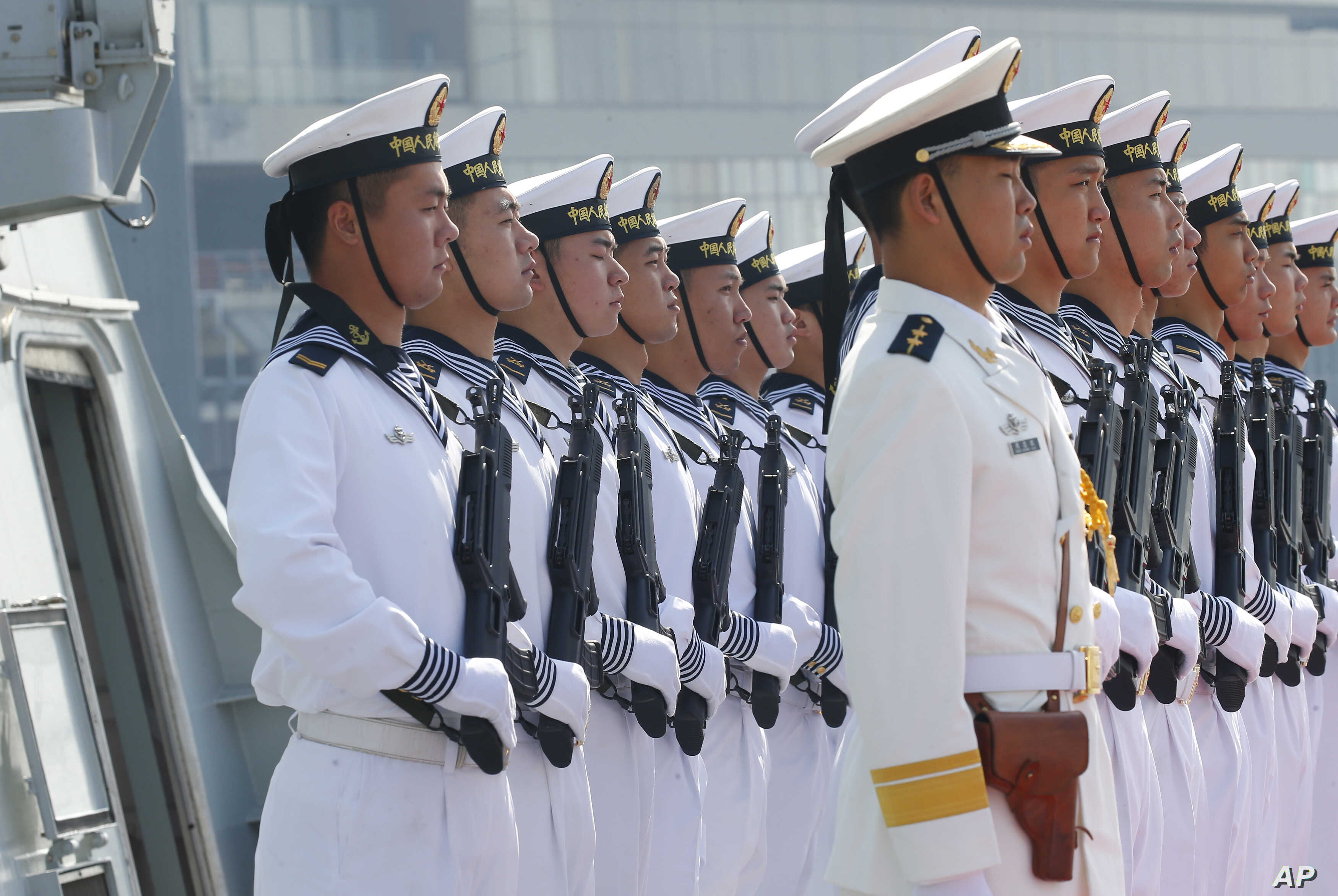 """Chinese People's Liberation Army Navy troops stand in formation on the deck of a type 054A guided missile frigate """"Wuhu"""" as it docks at Manila's South Harbor for a four-day port call, Jan. 17, 2019 in Manila, Philippines."""
