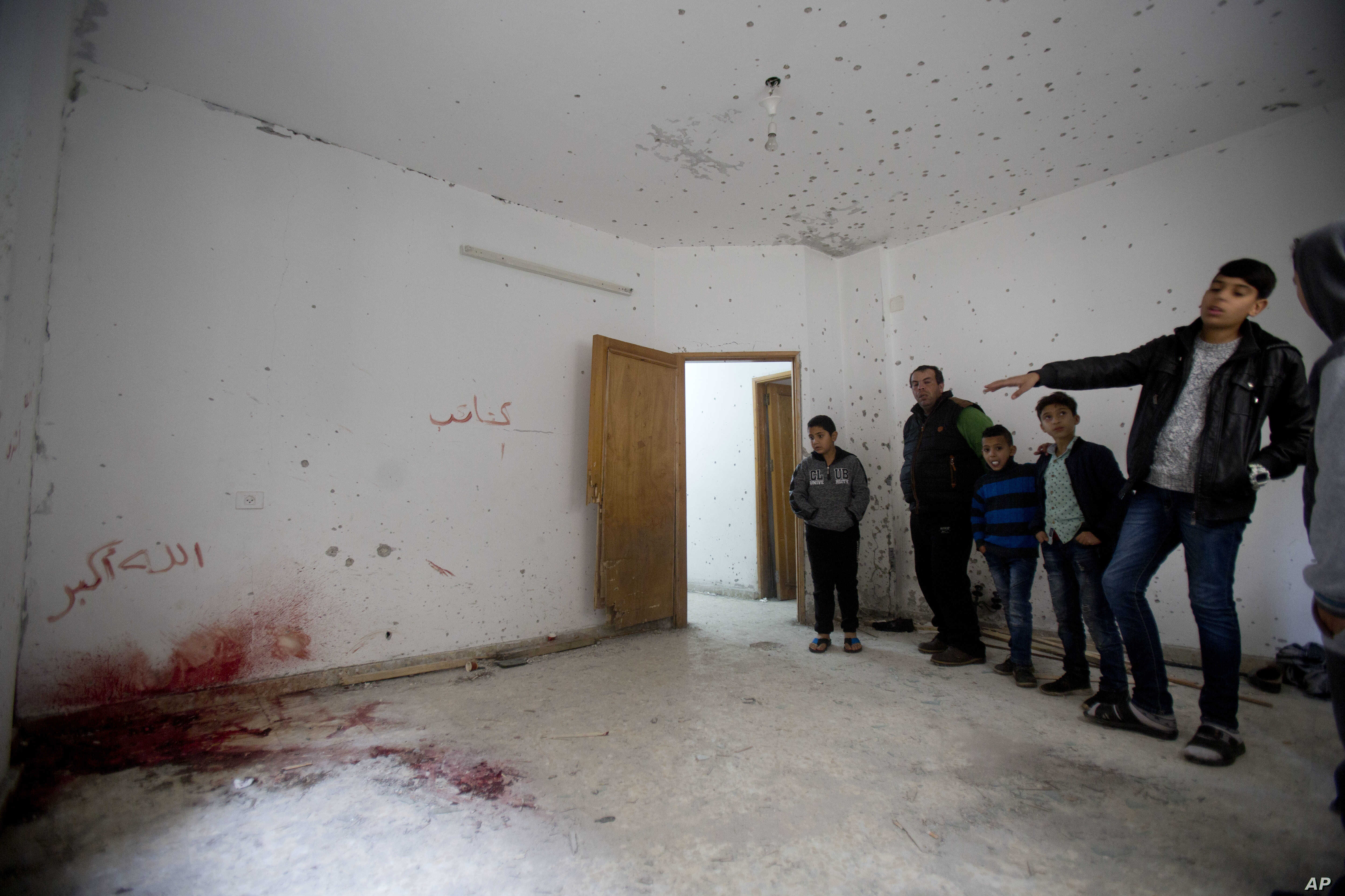 Palestinians look at a damage after an Israeli raid killed Ashraf Naalweh during an arrest raid in the Asker refugee camp near the West Bank city of Nablus, Thursday, Dec. 13, 2018.