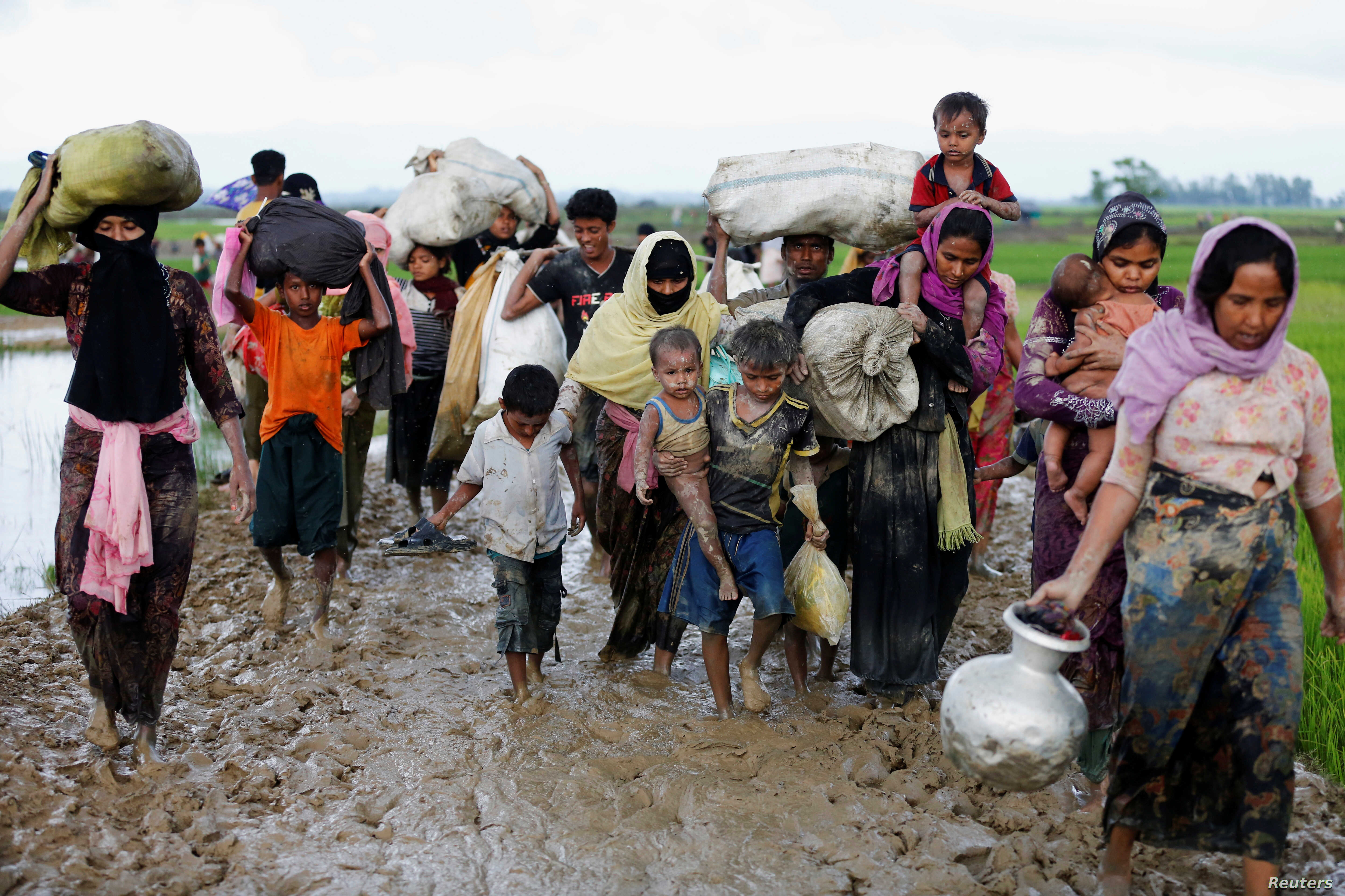A group of Rohingya refugees walk on the muddy road after traveling over the Bangladesh-Myanmar border in Teknaf, Bangladesh, Sept. 1, 2017.