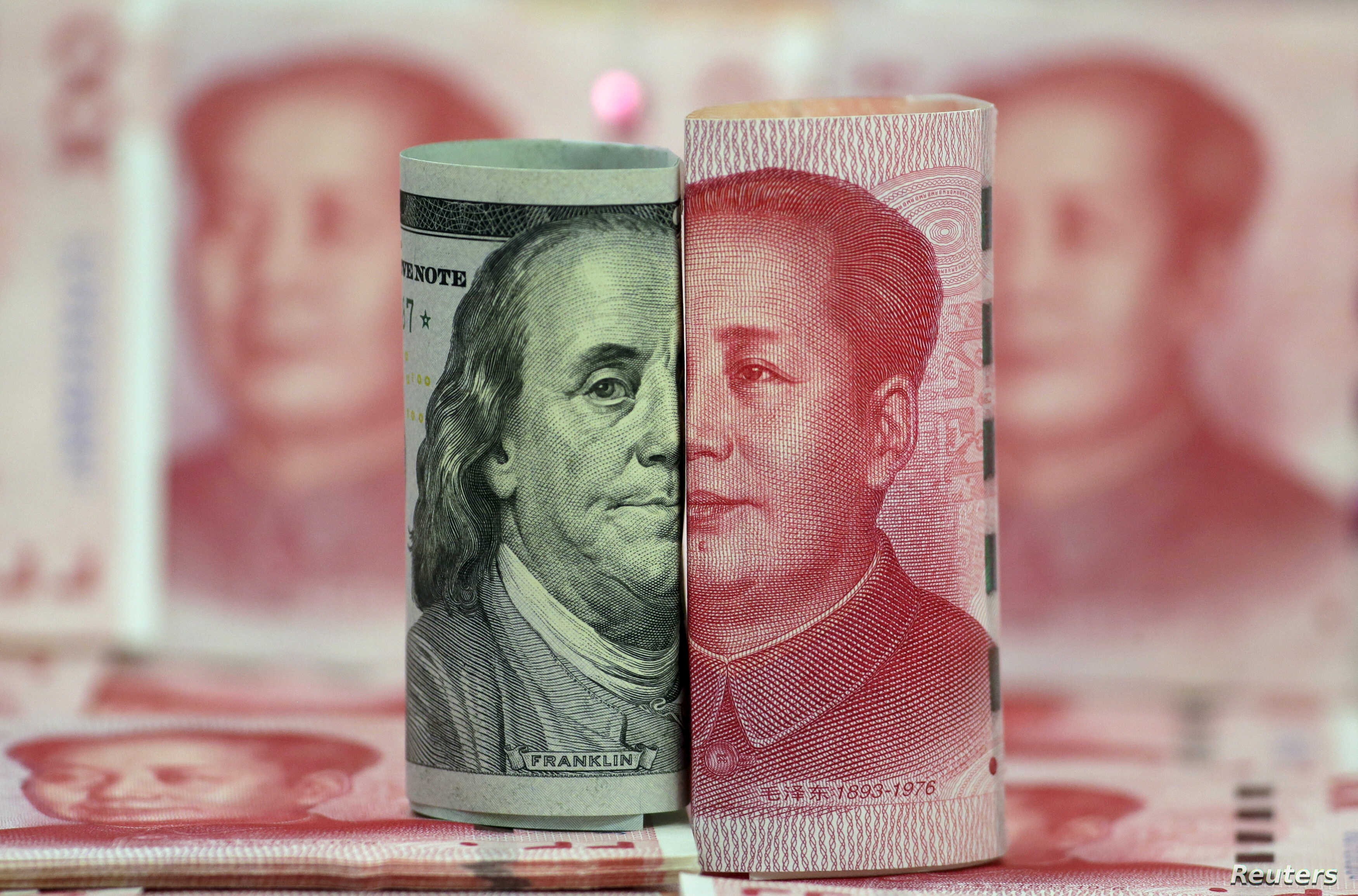 FILE -  U.S. 100-dollar banknote featuring American founder Benjamin Franklin and a Chinese 100-yuan banknote featuring late Chinese chairman Mao Zedong are seen in this picture illustration.