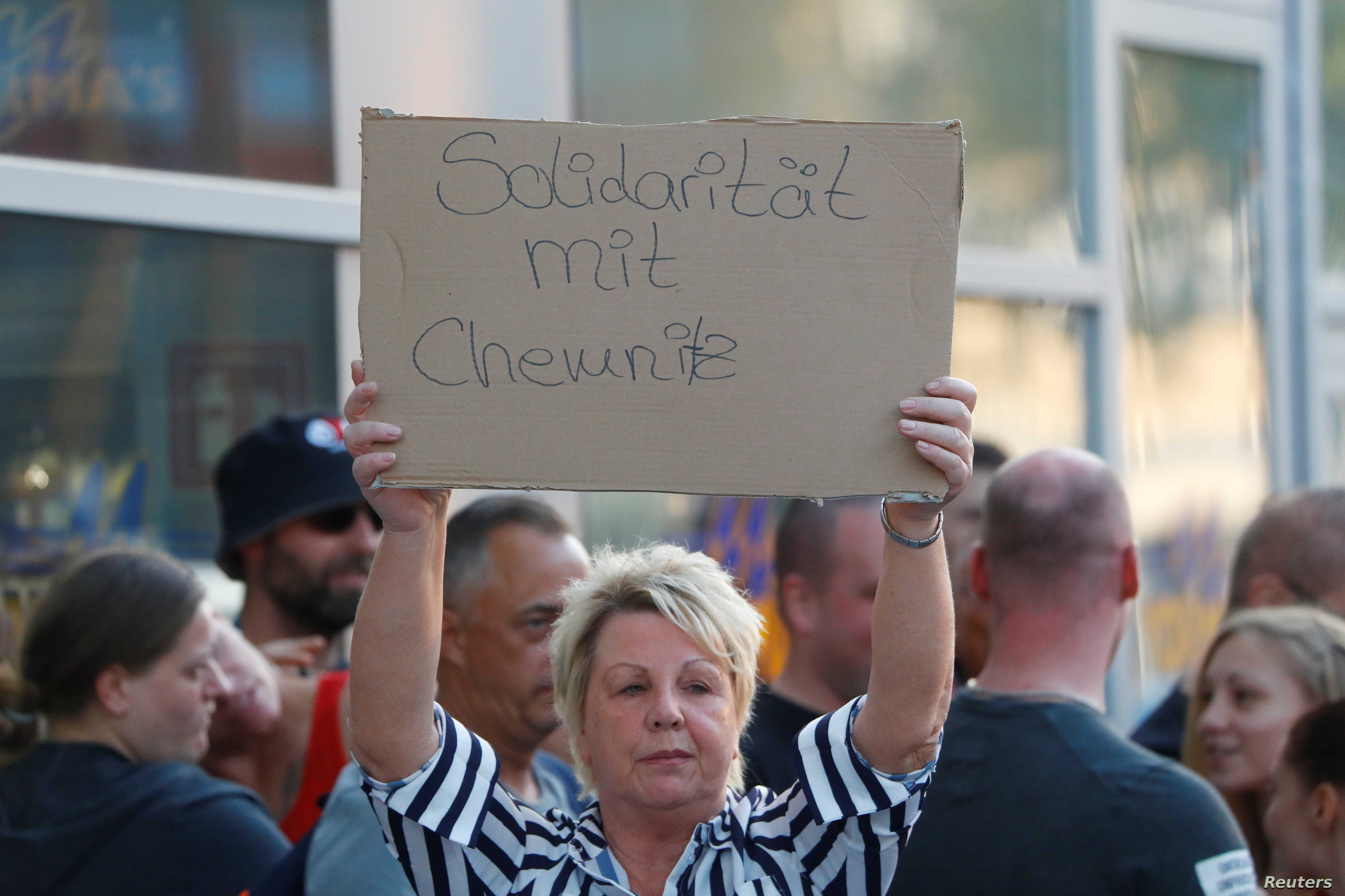"Demonstrators hold banners during a protest in Cologne, Germany, Aug. 28, 2018.  The banner reads, ""Solidarity with Chemnitz."""