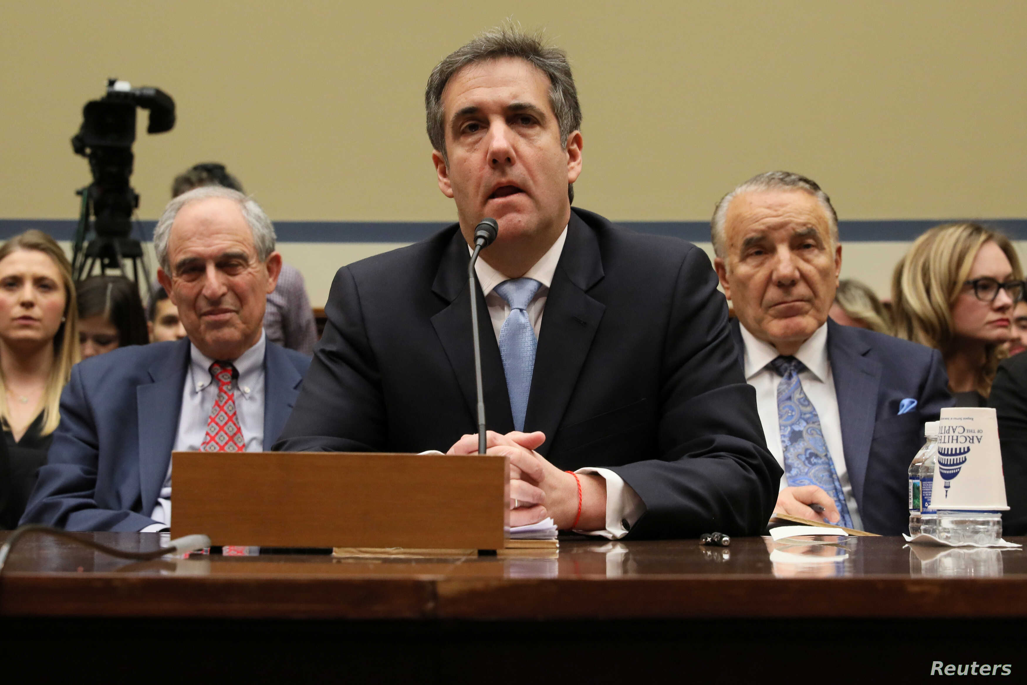 Michael Cohen, the former personal attorney of U.S. President Donald Trump, is flanked by his attorneys Lanny Davis (L) and Mike Monico (R) as he testifies before a House Committee on Oversight and Reform hearing on Capitol Hill in Washington, Feb. 2...