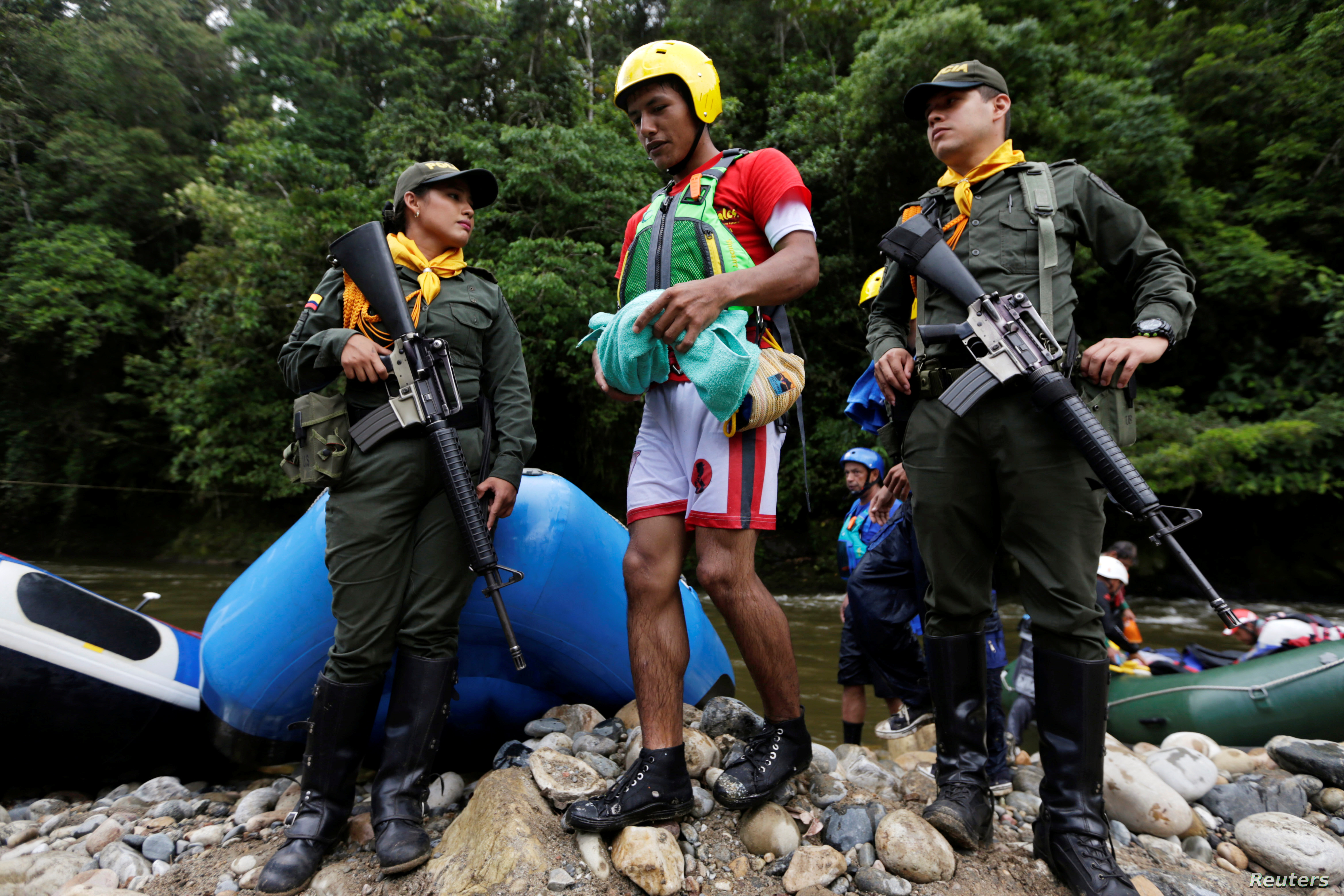 An ex-rebel of the FARC and now rafting instructor leaves his raft between members of the police in Miravalle, Colombia, Nov. 9, 2018.