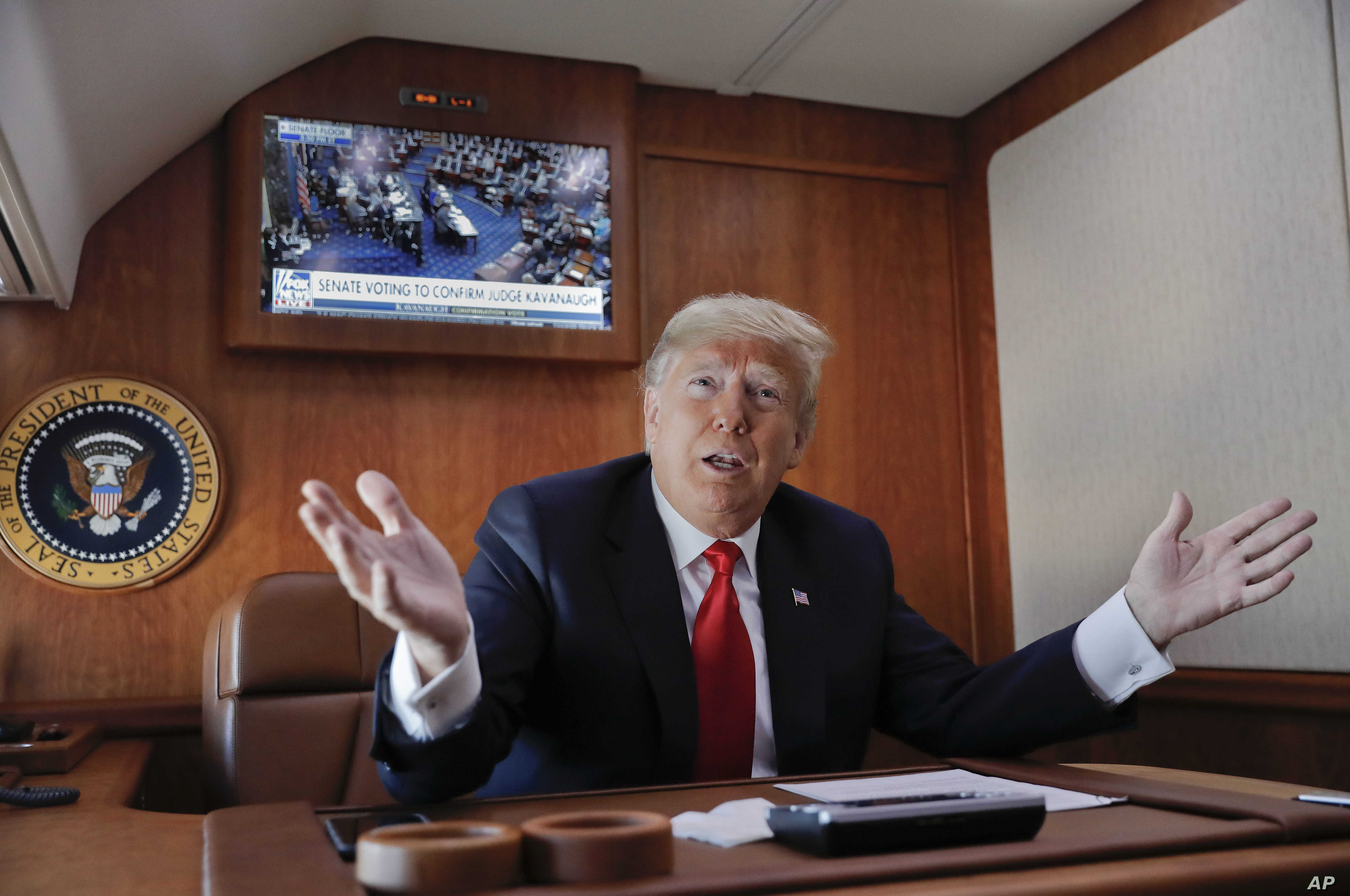 President Donald Trump, on board Air Force One, gestures while watching a live television broadcast of the Senate confirmation vote of Supreme Court nominee Brett Kavanaugh, Oct. 6, 2018. Trump was traveling from Washington to Topeka, Kan., for a cam...
