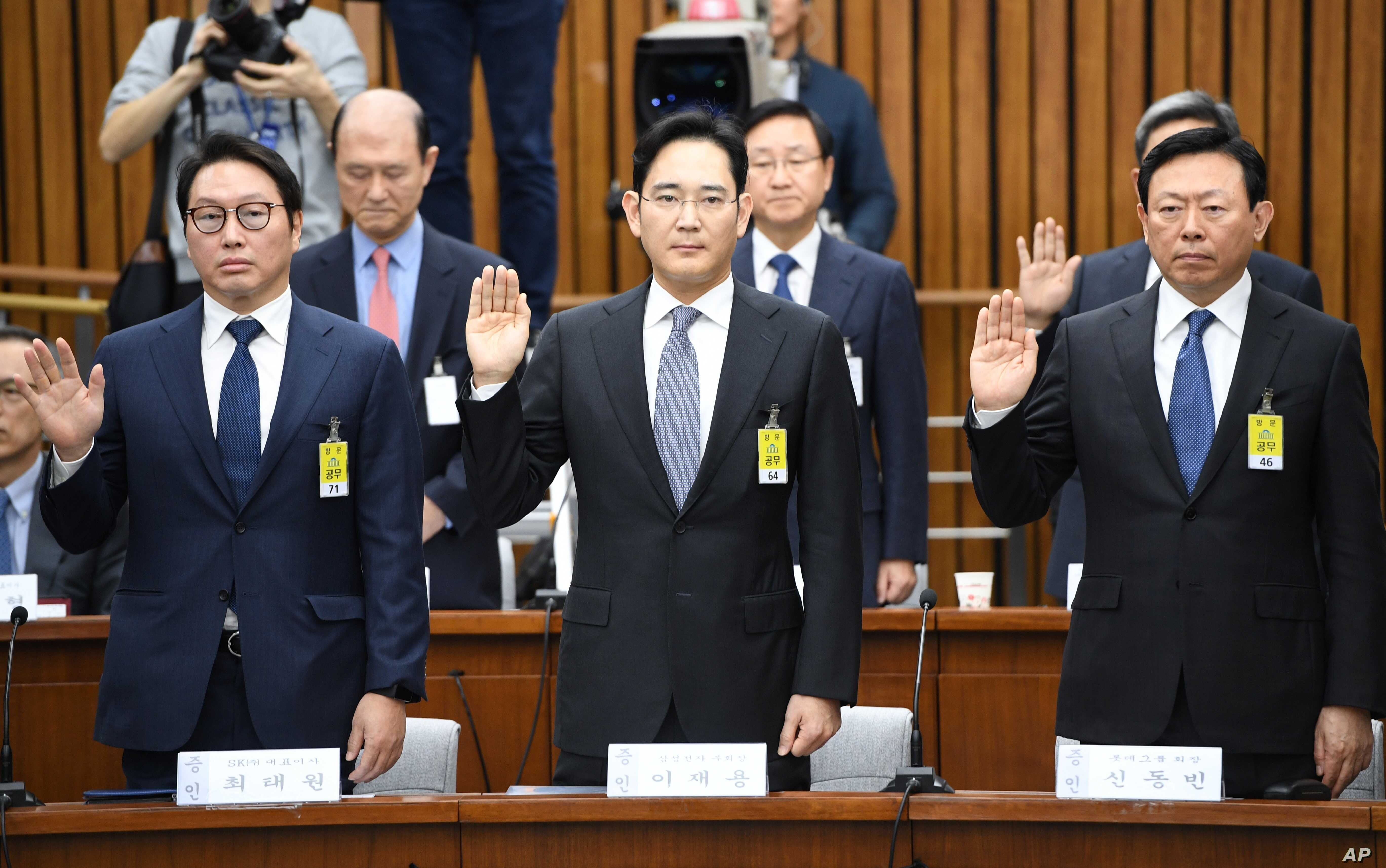 SK Group chairman Chey Tae-Won, left, Samsung Electronics Vice Chairman Lee Jae-yong, center,  and Lotte Group Chairman Shin Dong-Bin take an oath during a parliamentary probe into a scandal engulfing President Park Geun-hye at the National Assembly ...