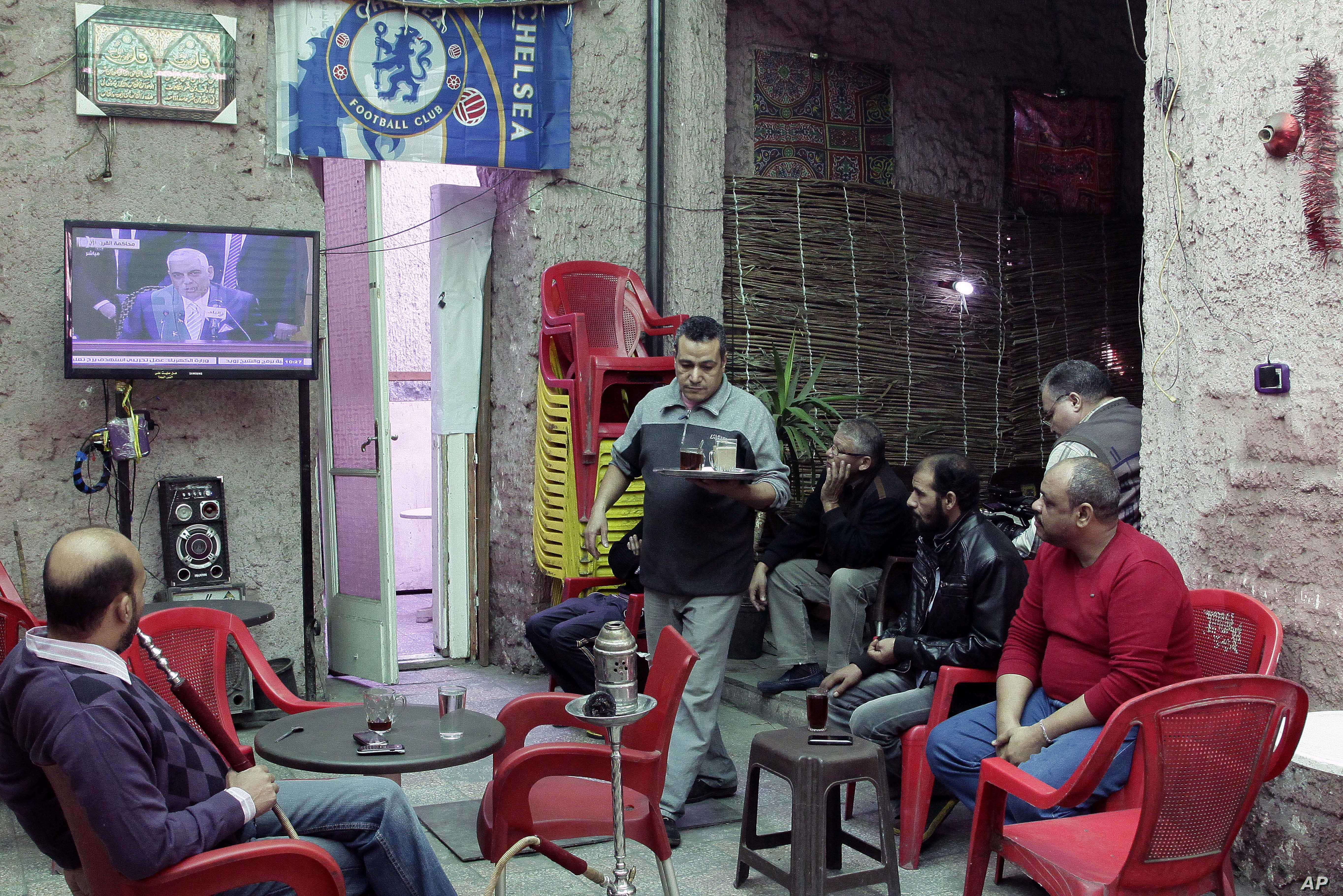 Egyptians gather in tea shop to watch a state television broadcast of the verdict case against the country's ousted President Hosni Mubarak Cairo, Egypt, Saturday, Nov. 29, 2014.