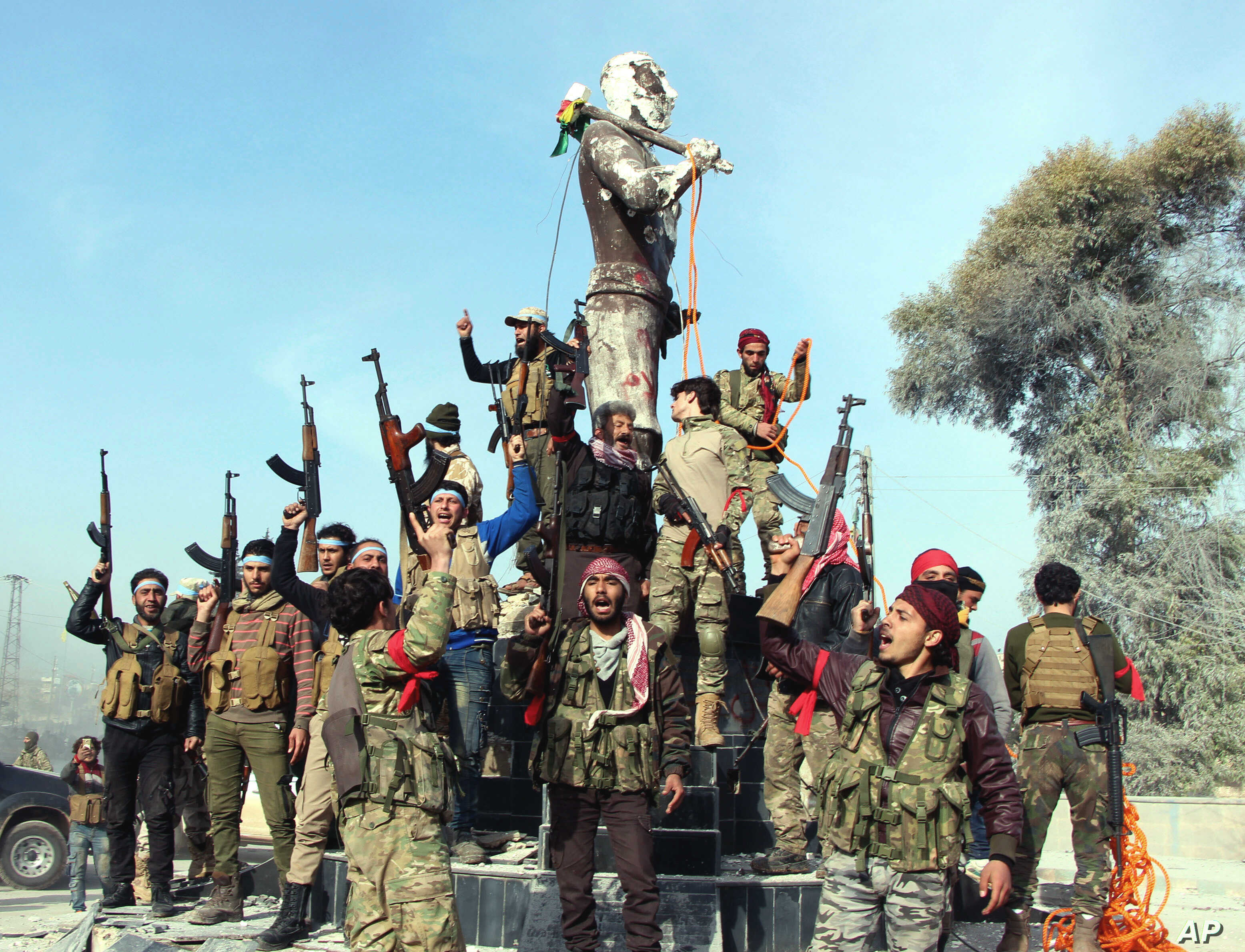 Turkey-backed Free Syrian Army soldiers celebrate around a statue of Kawa, a mythology figure in Kurdish culture as they prepare to destroy it in city center of Afrin, northwestern Syria,  March 18, 2018.