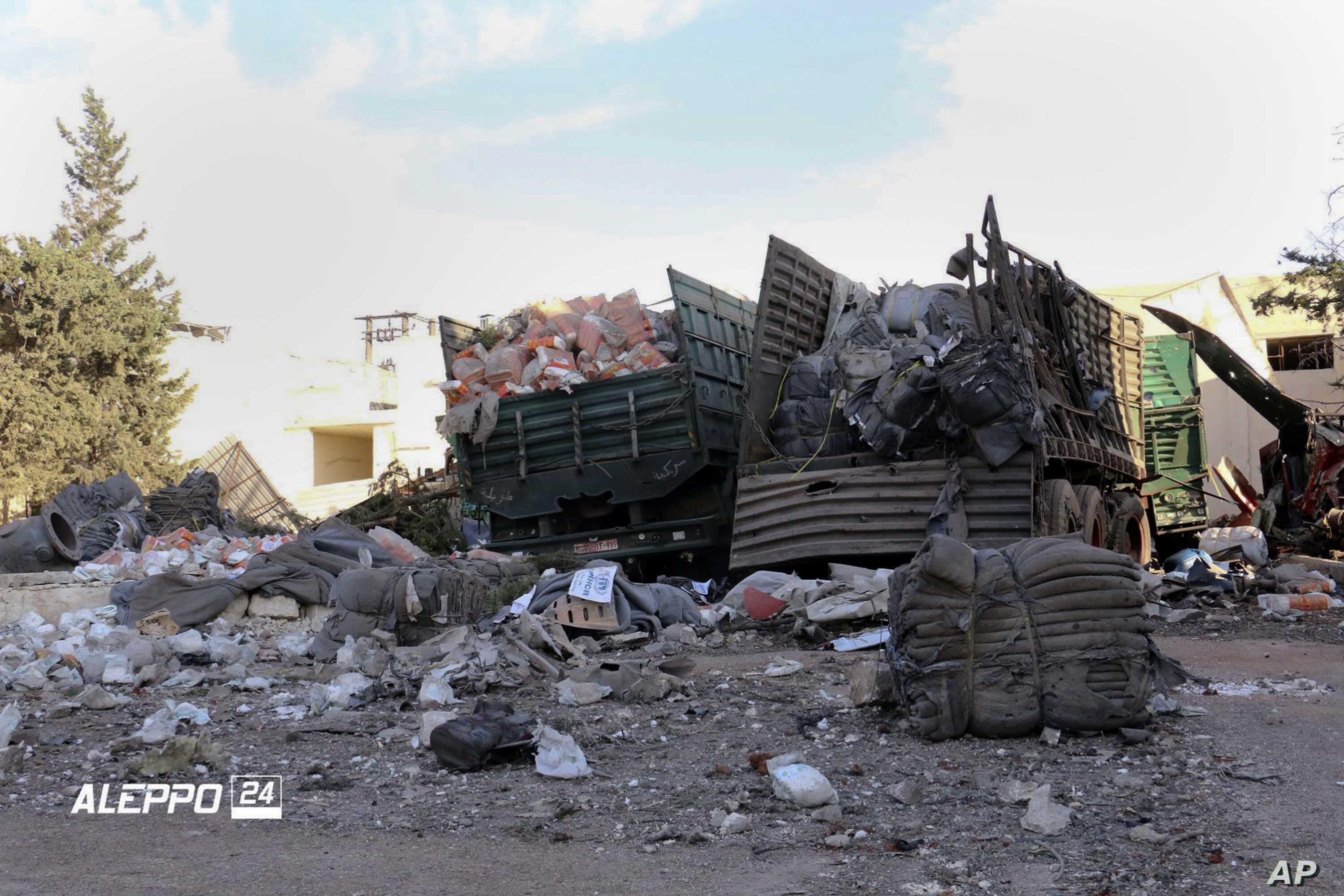 This image provided by the Syrian anti-government group Aleppo 24 news, shows damaged trucks carrying aid, in Aleppo, Syria, Sept. 20, 2016.
