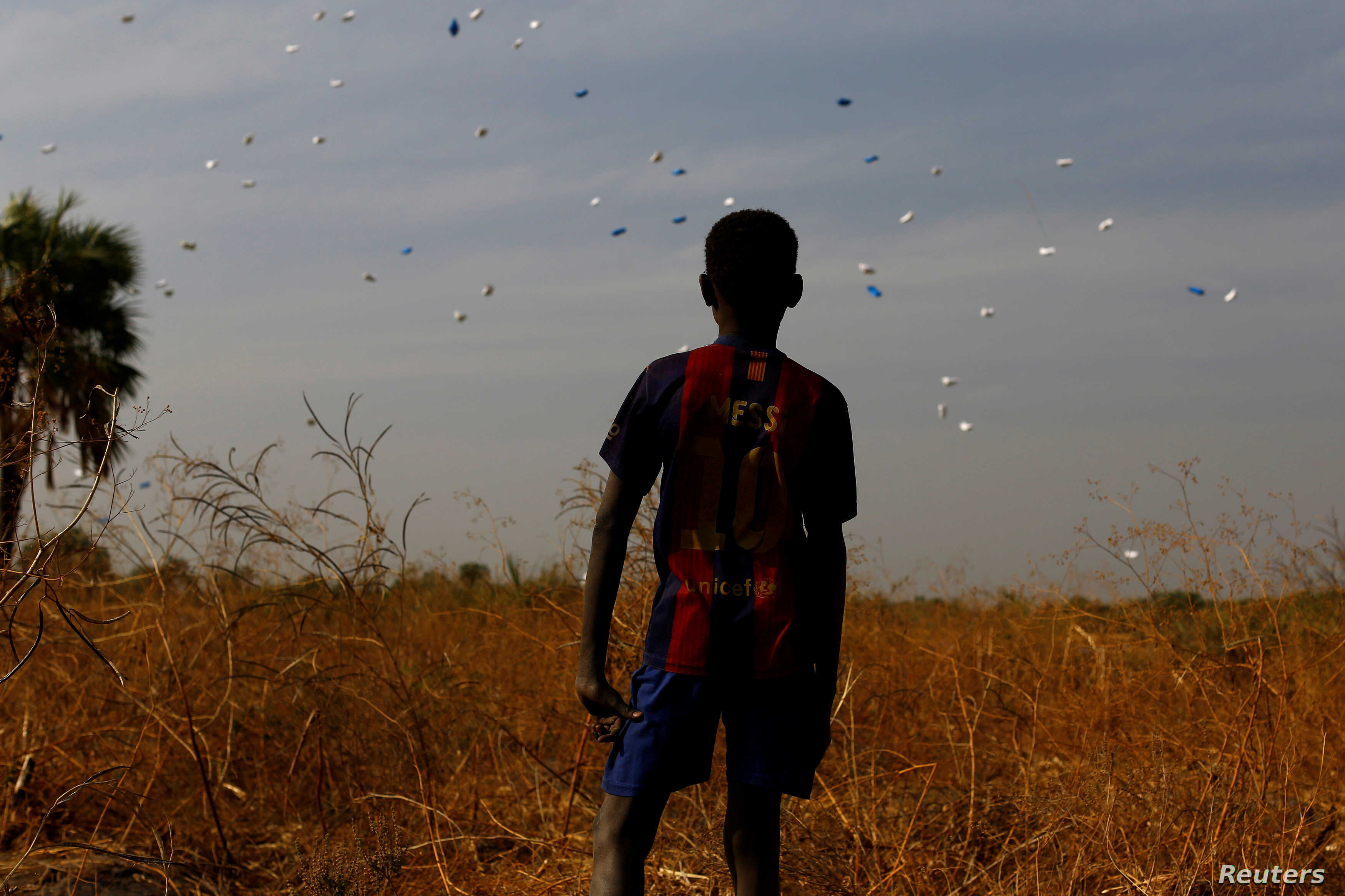 A boy watches sacks of food drop to the ground during a United Nations World Food Program airdrop close to Rubkuai, South Sudan, Feb. 18, 2017.