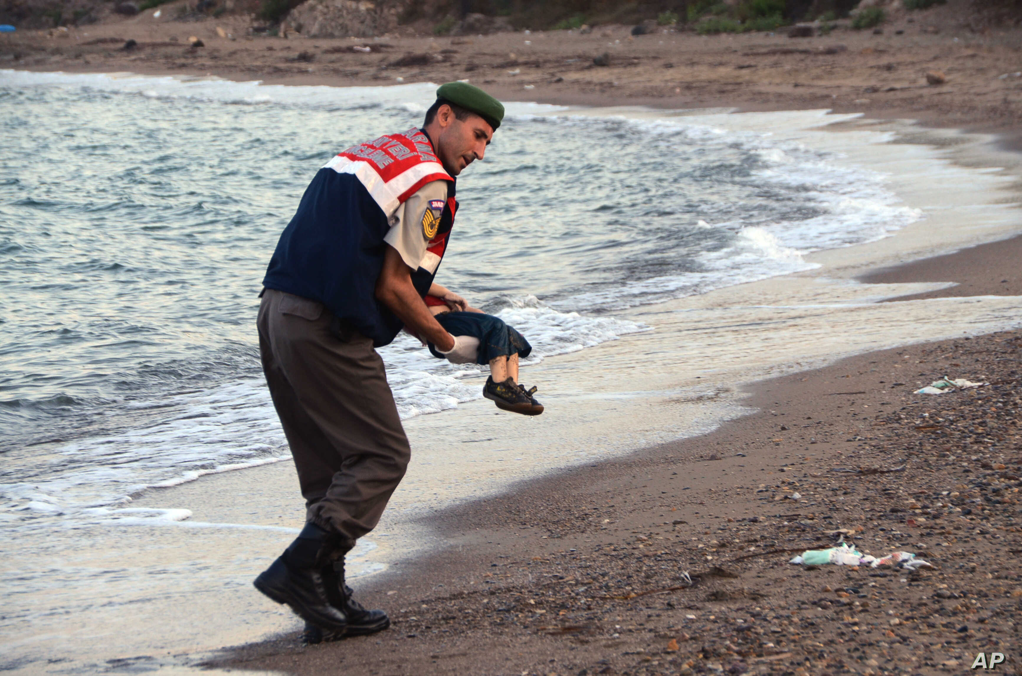 A paramilitary police officer carries the lifeless body of a  migrant child after a number of migrants died and a smaller number  were reported missing after boats carrying them to the Greek island of Kos capsized, near the Turkish resort of Bodrum, ...