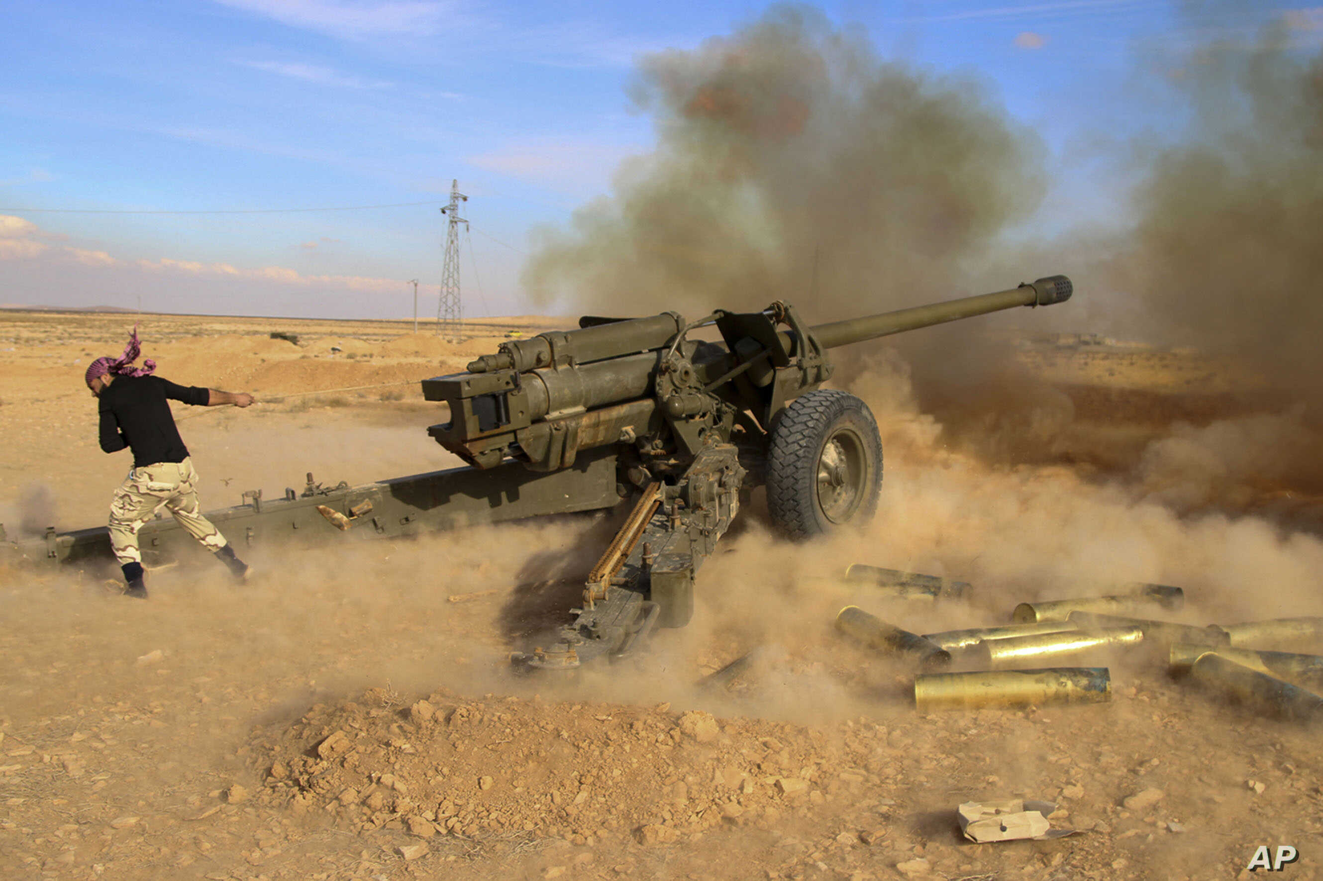 FILE - Syrian government troops fire at Islamic State group positions near Mahin, Syria, Jan. 30, 2016.