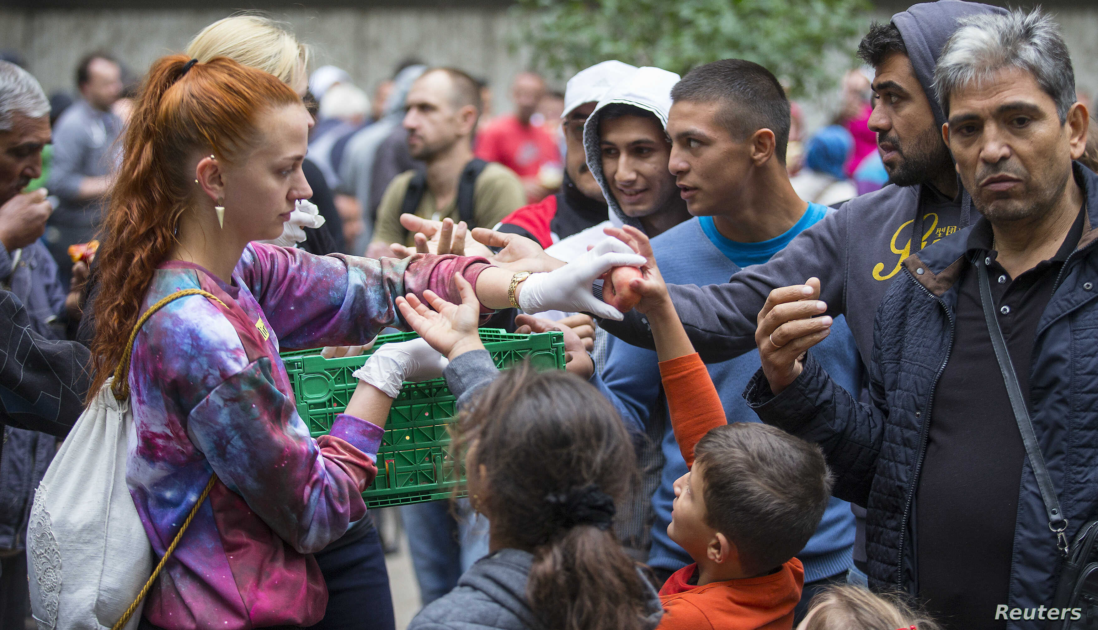 A helper distributes fruit to migrants in front of the State Office for Health and Social Affairs (LaGeSo), in Berlin, Germany, Sept. 3, 2015.