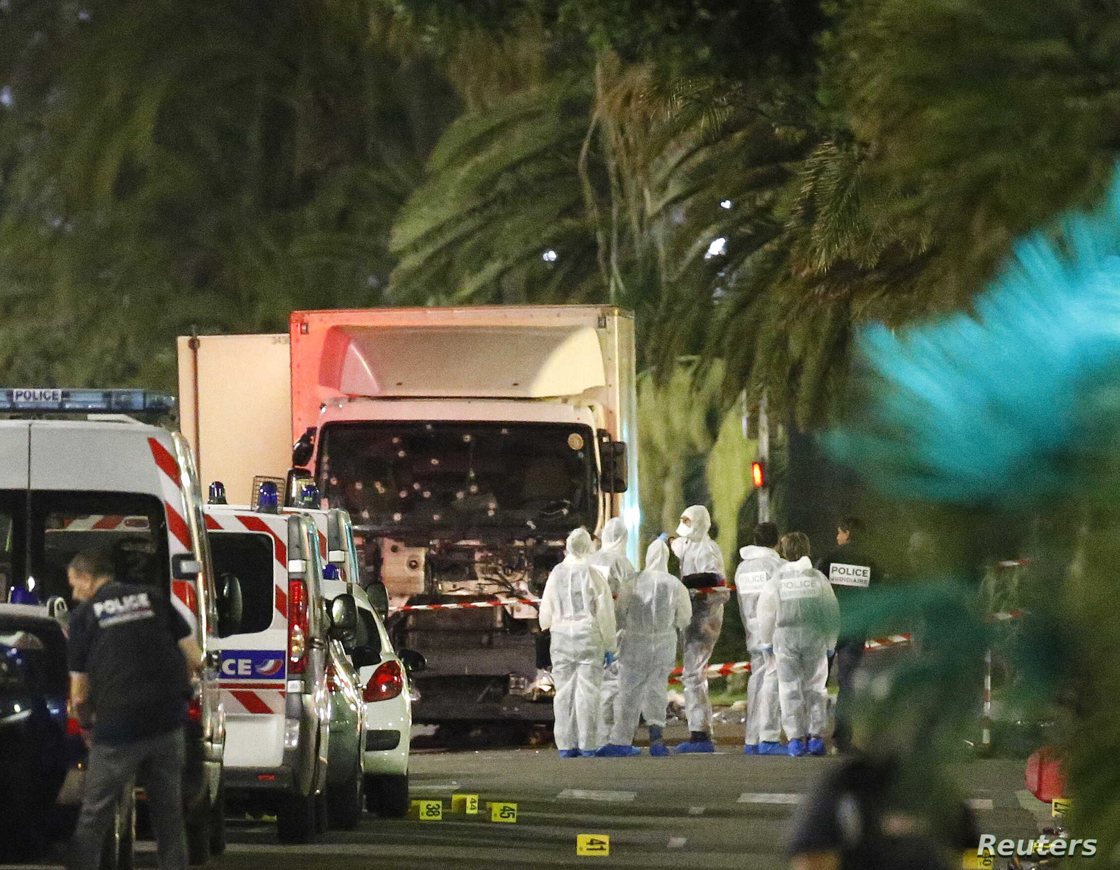 French police force and forensic officers early Friday look at the truck that ran into a crowd celebrating the Bastille Day national holiday, killing at least 77 people, in Nice, France, July 14, 2016.