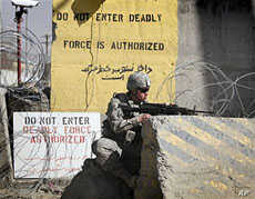 A US soldier controls the area outside the gate of a US base after an attack in Kabul, Afghanistan, April 2, 2011