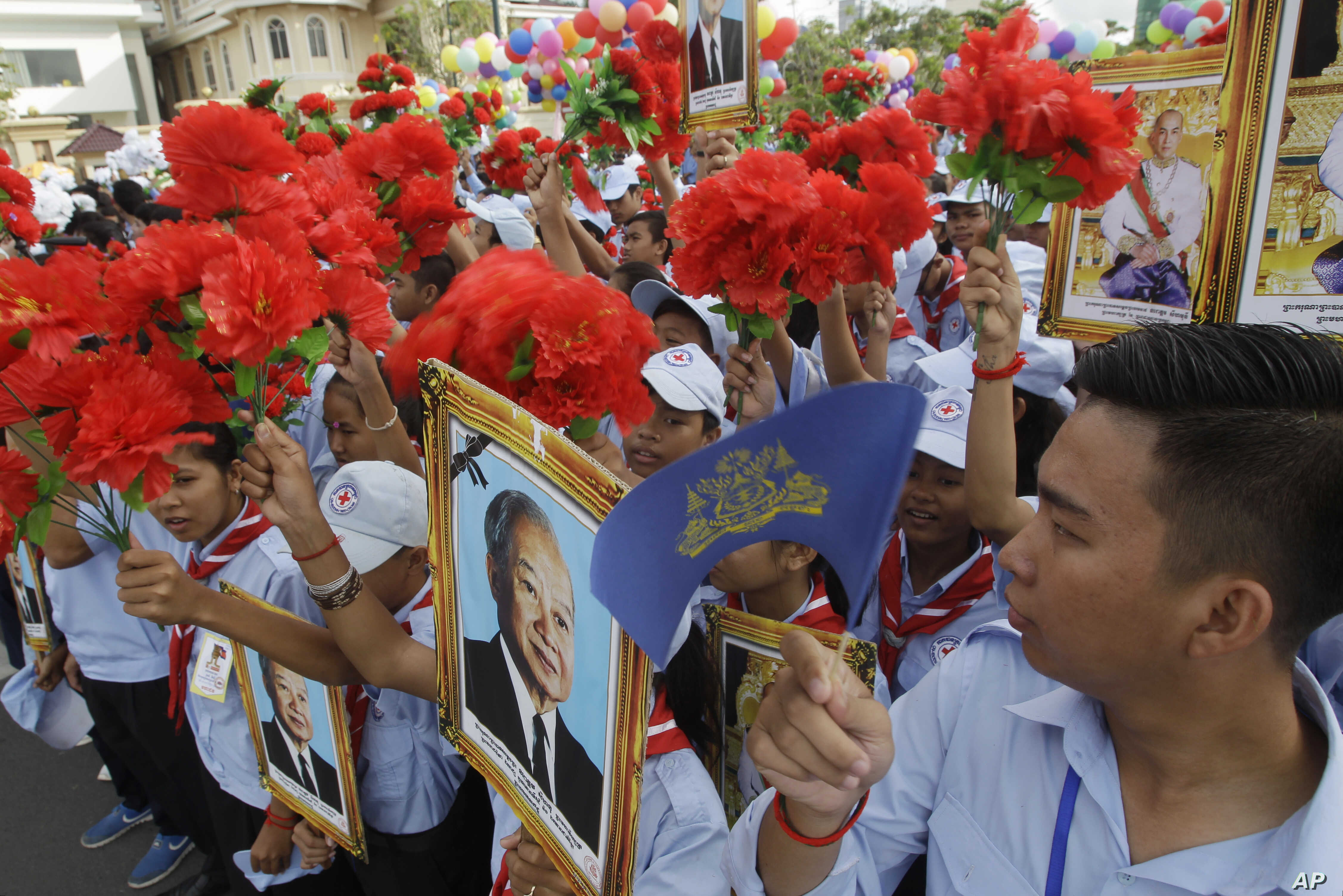 Cambodian students hold flowers and portraits of their king, Norodom Sihamoni, upper right, and former king, Norodom Sihanouk, center, during Independence Day celebrations in Phnom Penh, Cambodia, Nov. 9, 2017.