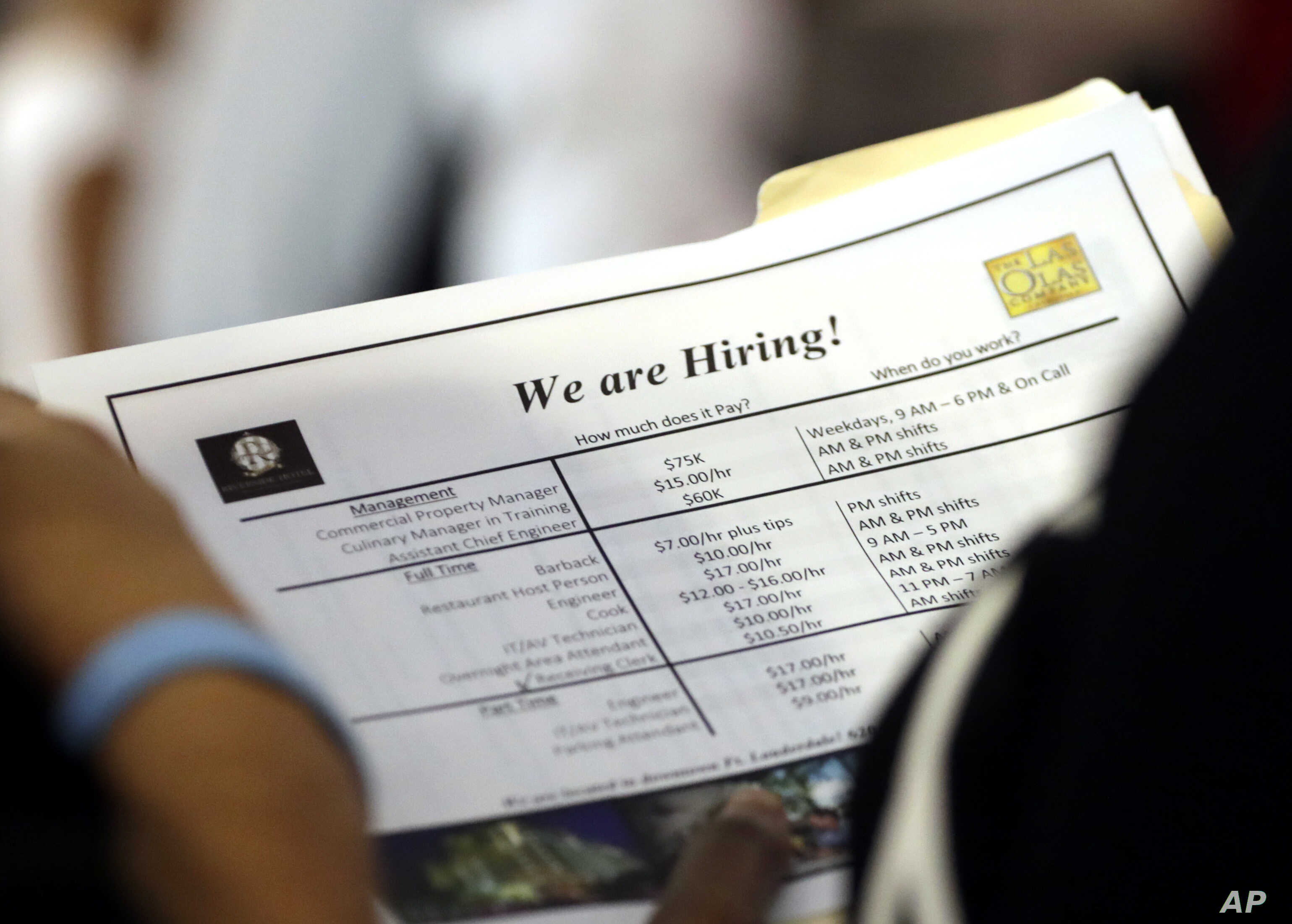 In this Thursday, June 21, 2018 photo, a job applicant looks at job listings for the Riverside Hotel at a job fair hosted by Job News South Florida, in Sunrise, Fla.