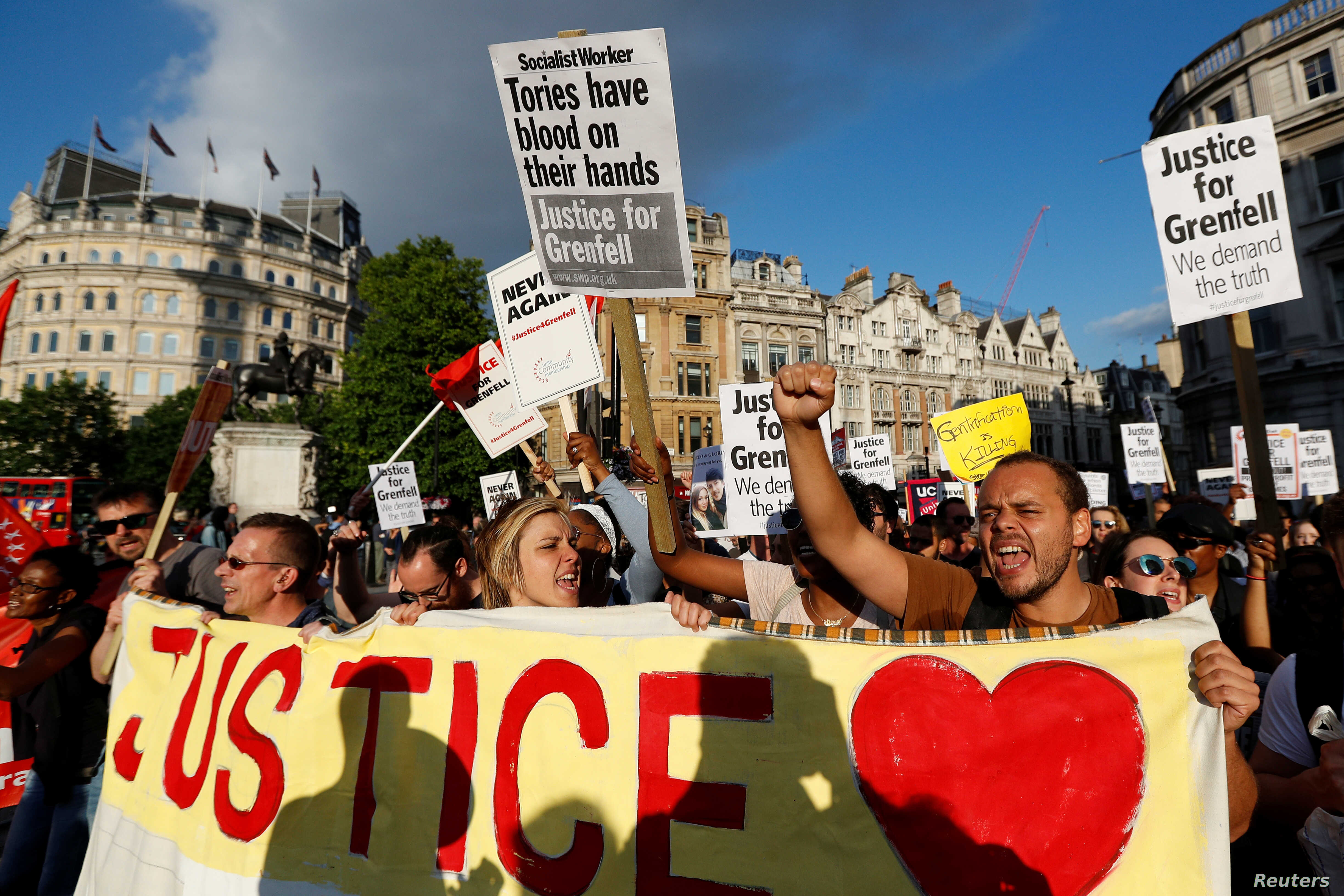 Demonstrators hold up banners during a march in Westminster, following the fire that destroyed The Grenfell Tower block, in north Kensington, West London, Britain, June 16, 2017.